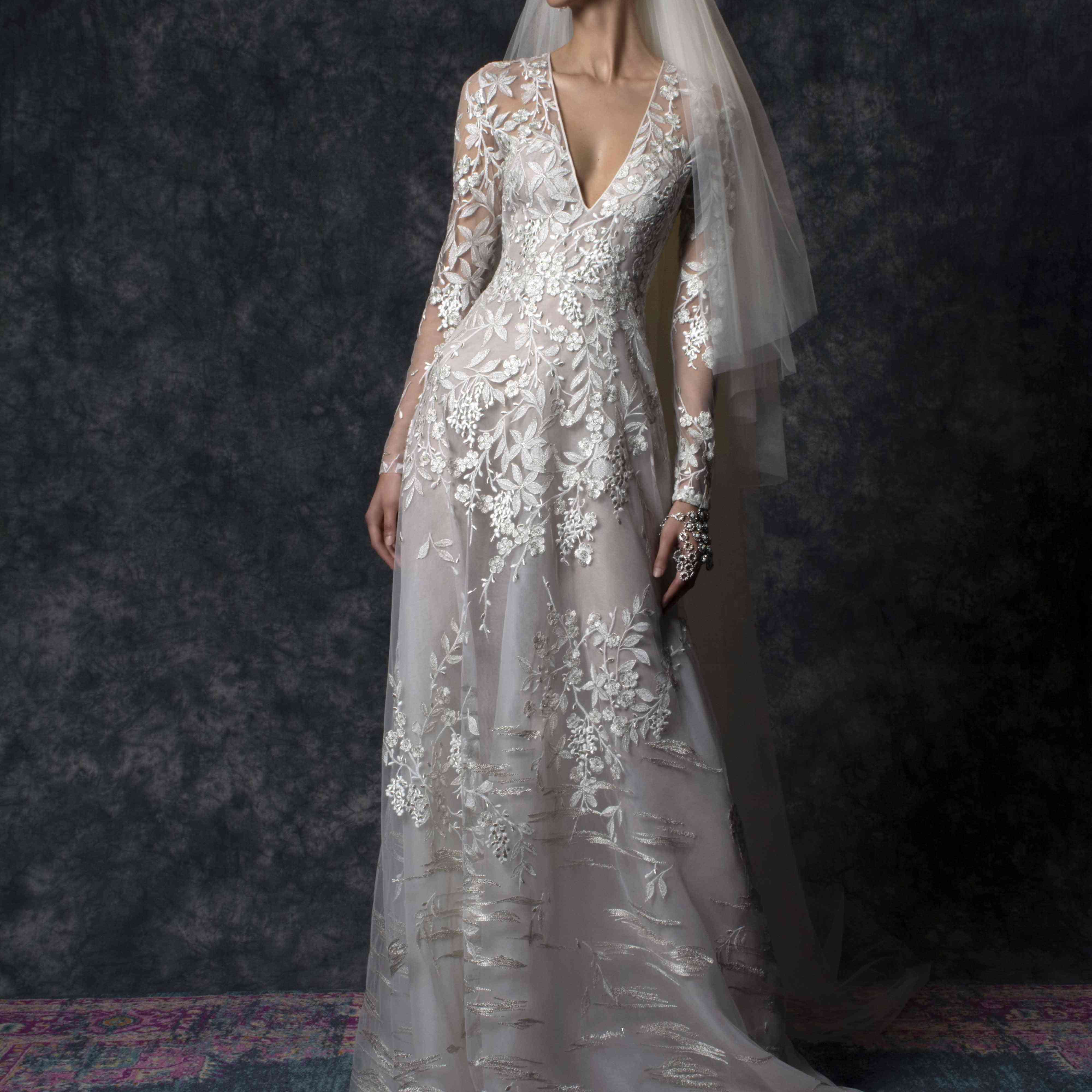 Model in long-sleeve V-neck gown with floral embroidery