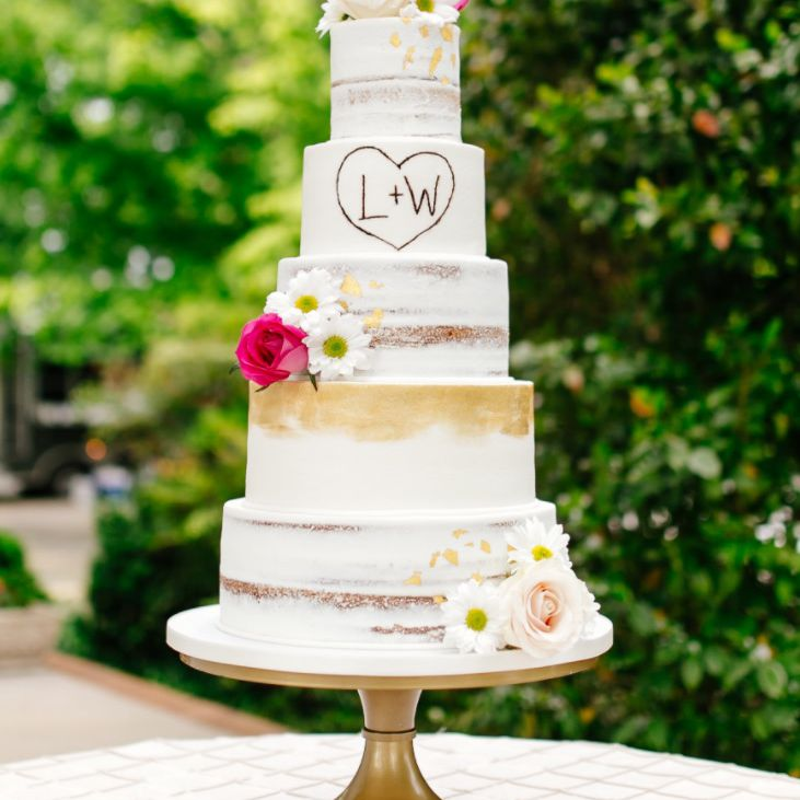 Tall wedding cake with naked layers and bright pink flower