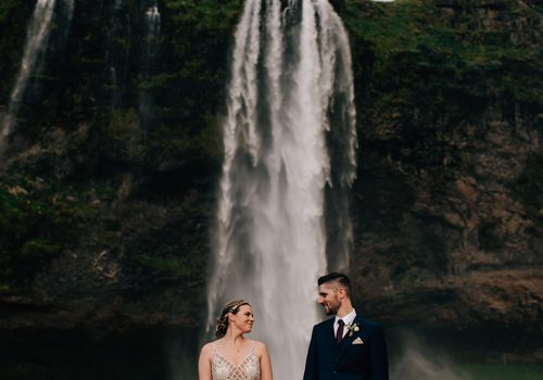 Couple holding hands in front of a waterfall in Iceland