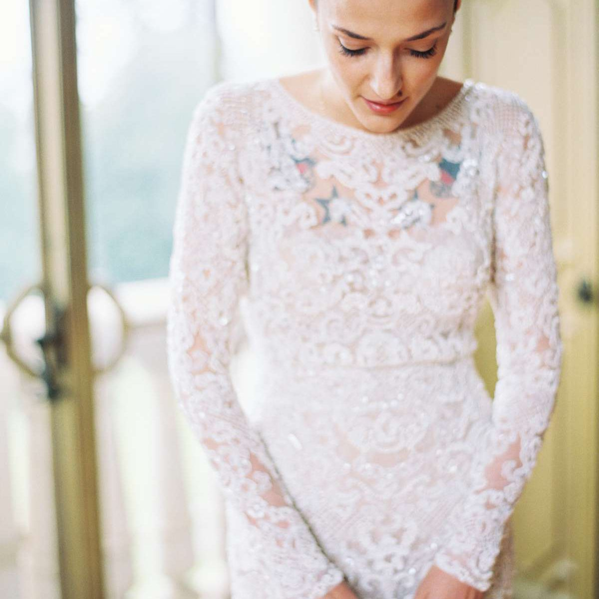 Tattooed bride wearing a sheer lace dress