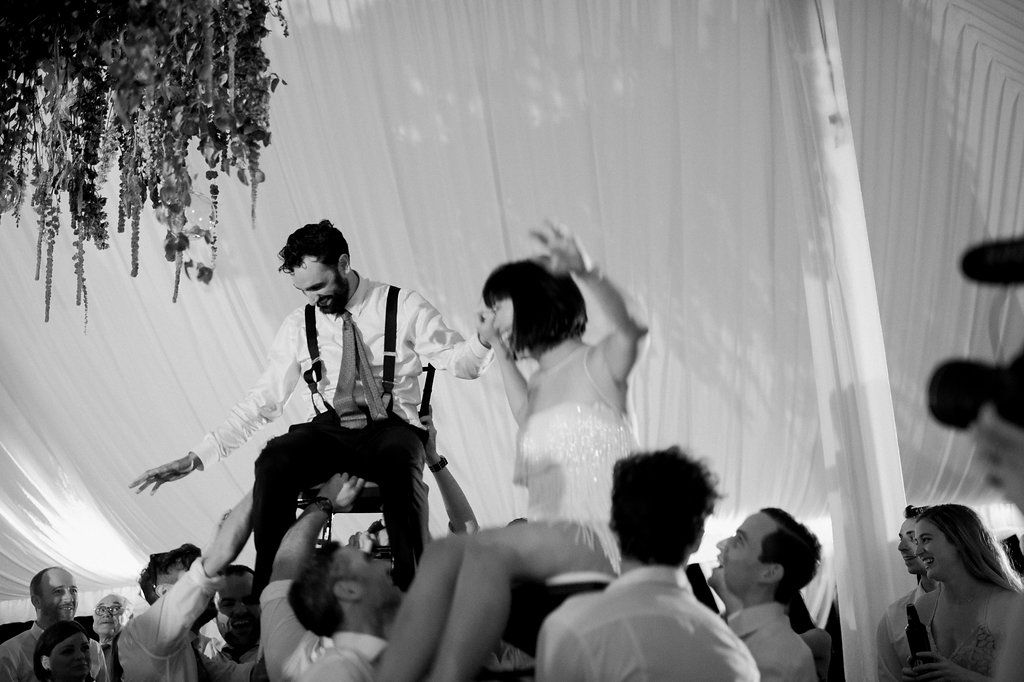 Bride and groom lifted in chairs