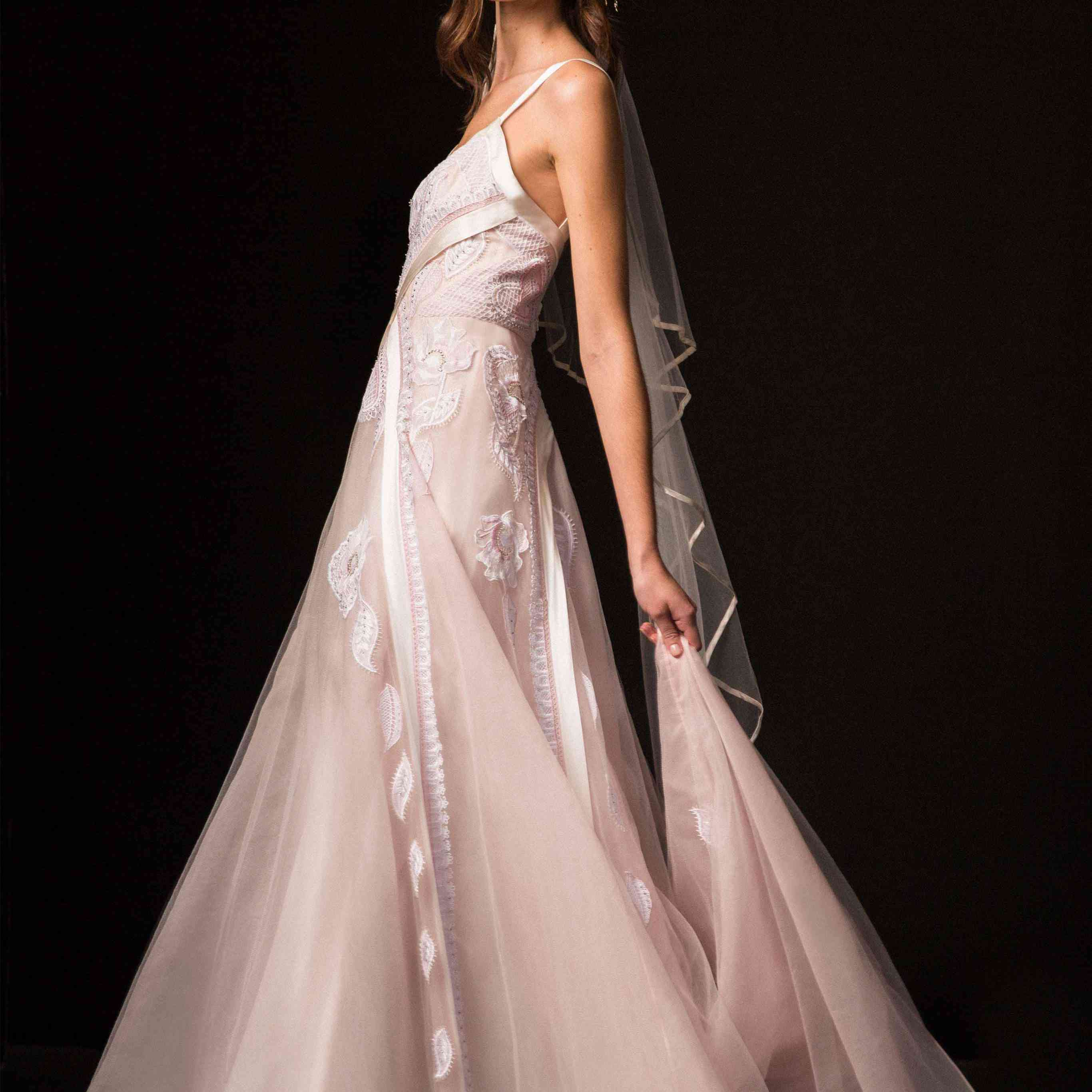 Model in blush pink tulle gown with flower and heart lattices