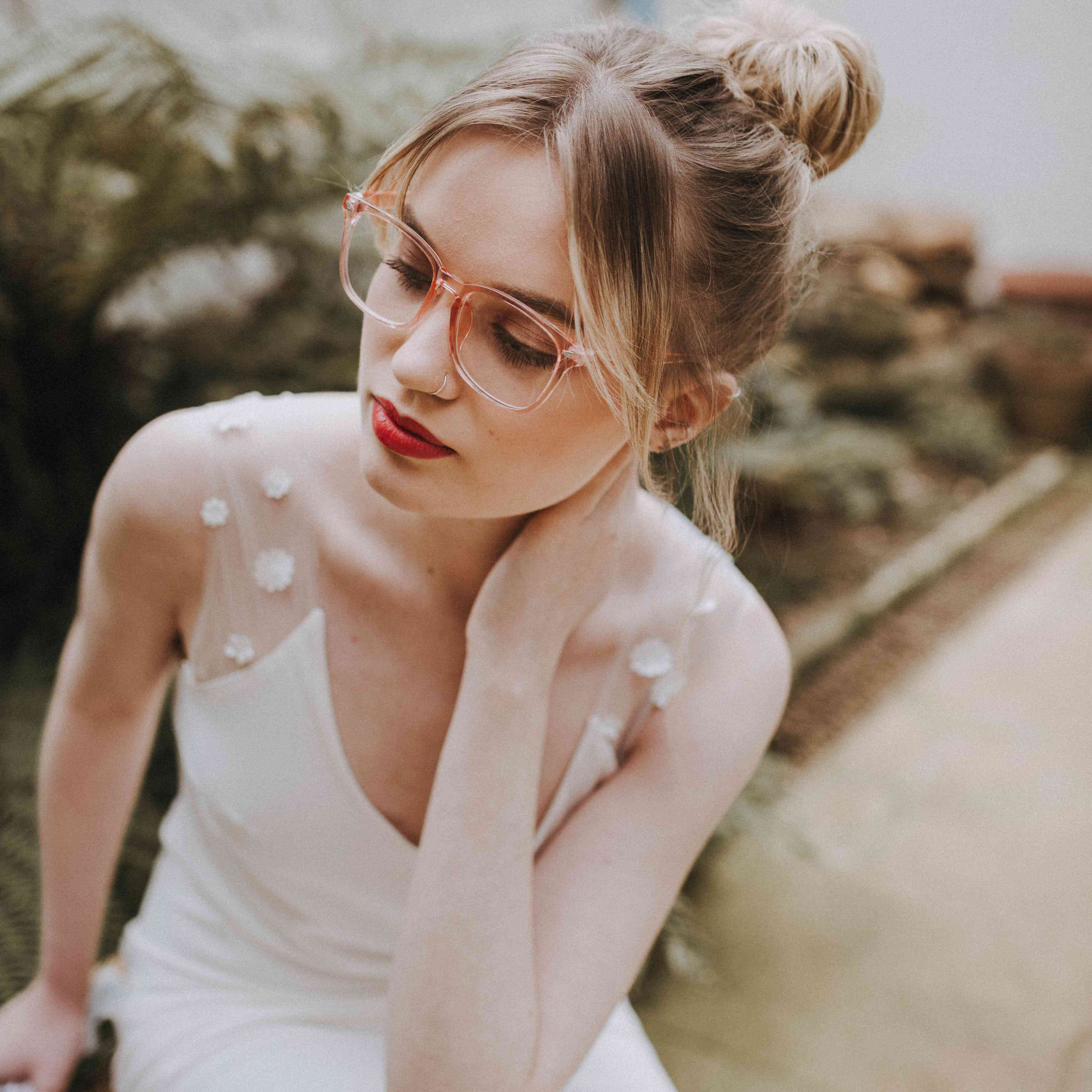 Bride in white gown with her hair in a bun wearing glasses and red lipstick