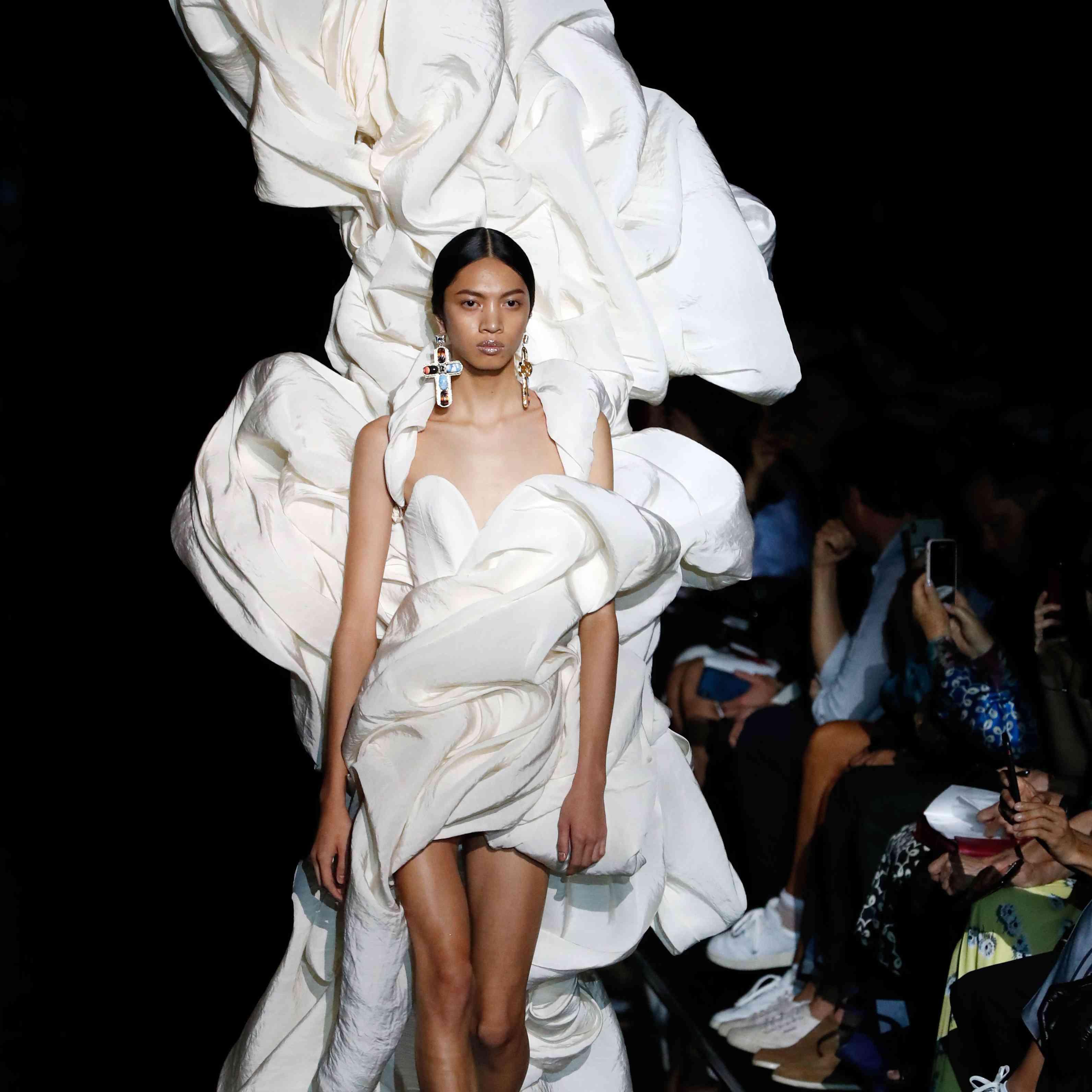 Model walking runway in large white gown