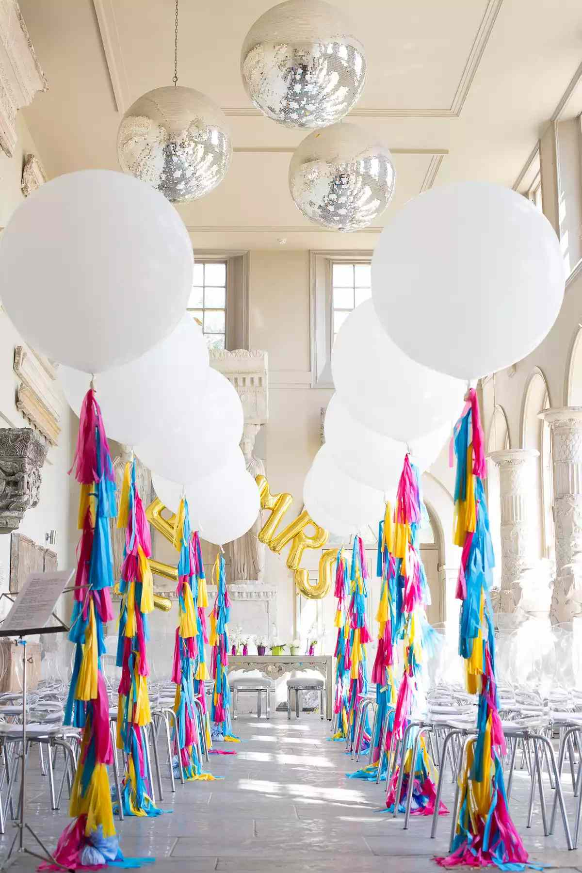 White balloons with colorful streamers as aisle markers