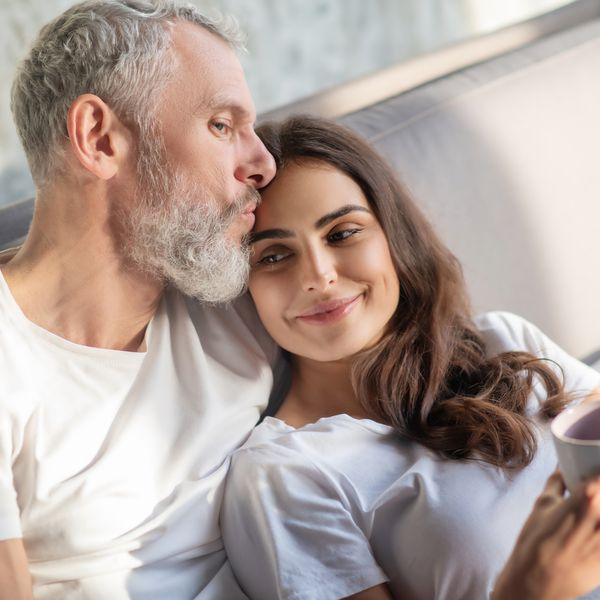 Couple smiling and having coffee in bed