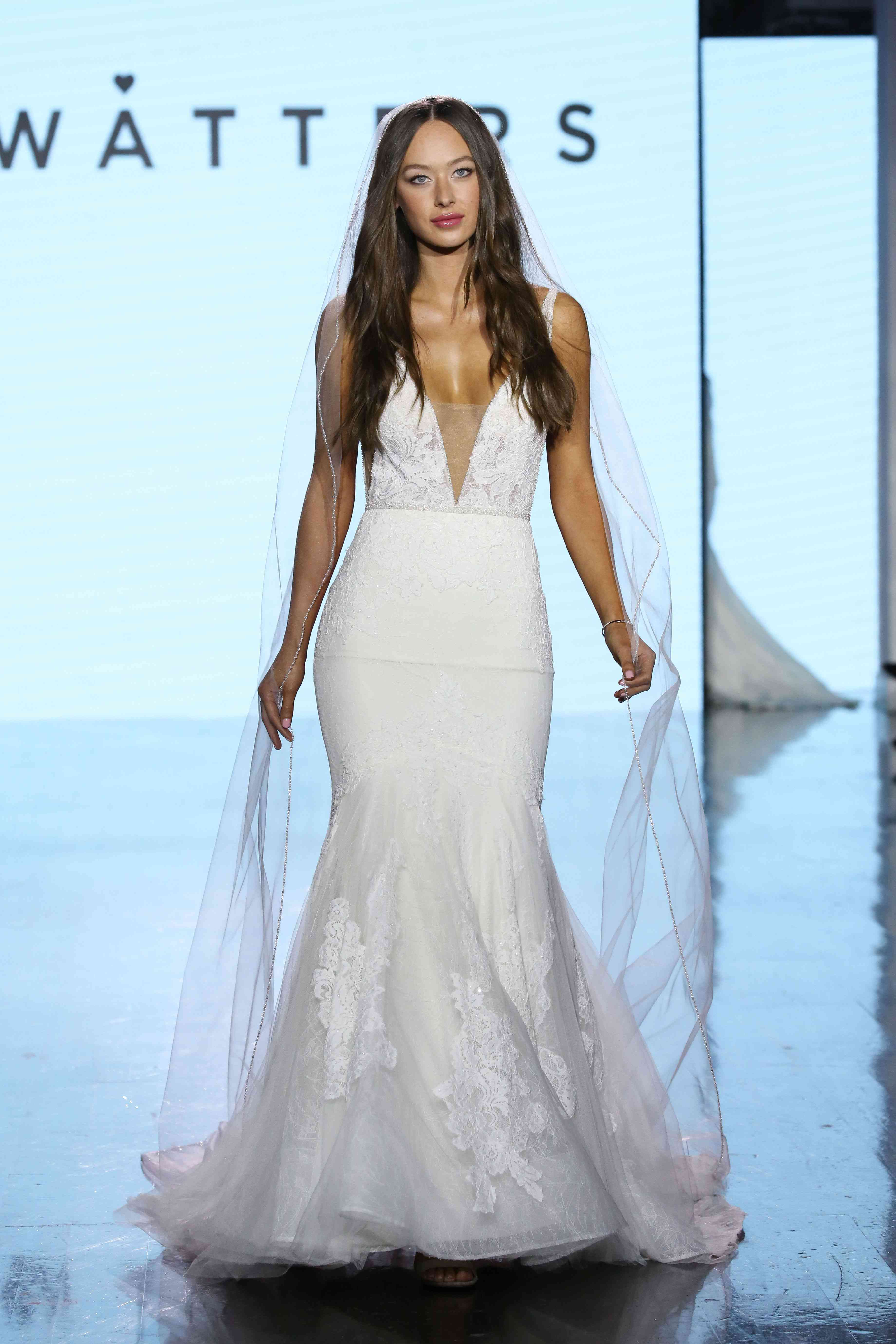 Model on runway in a floral lace V-neck trumpet wedding gown