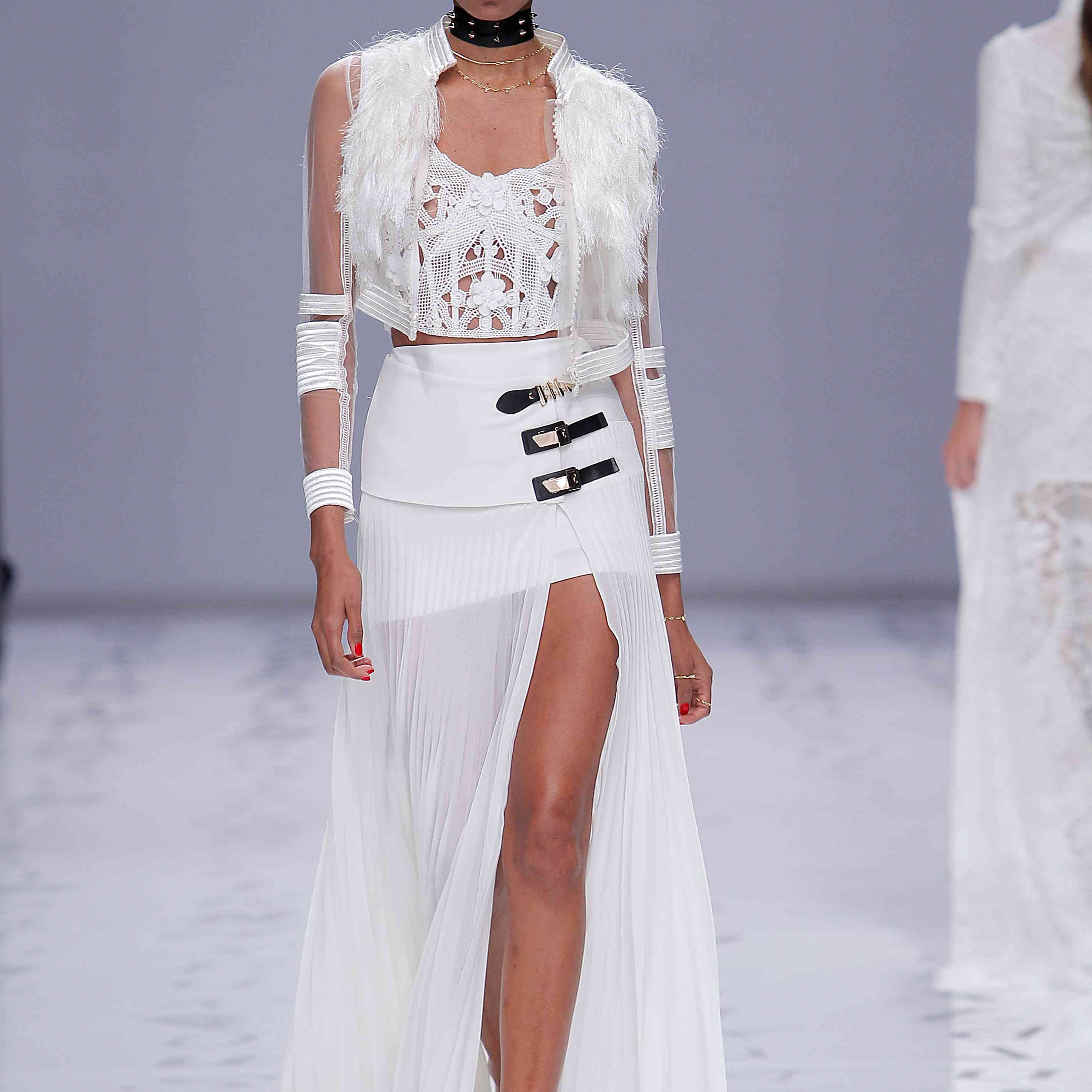 Model in a knit crop top with floral appliques and silk organza cropped jacket with feather accents and high-waisted chiffon skirt with a high slit and black and gold buckle details at the side