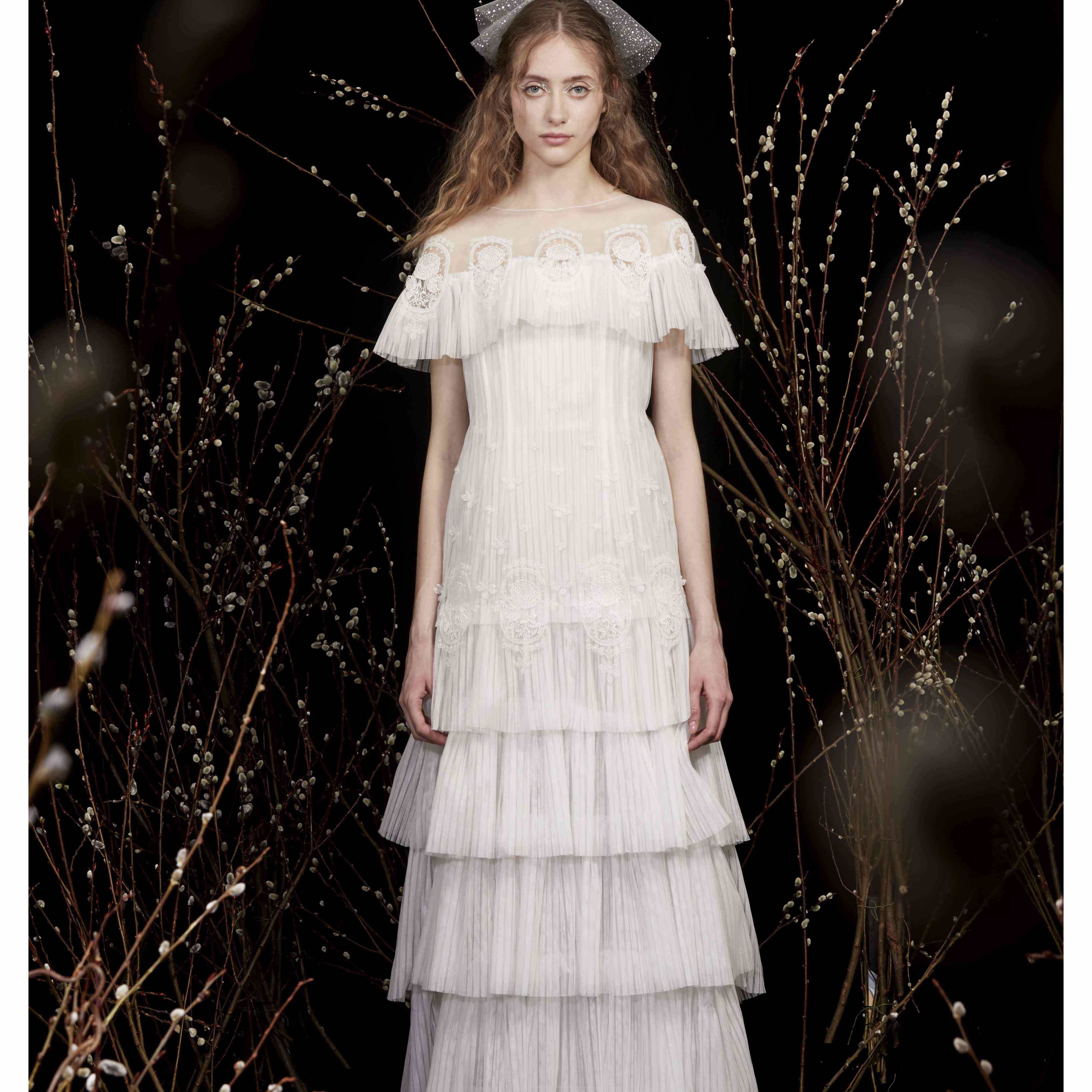Model in tiered capelet wedding dress