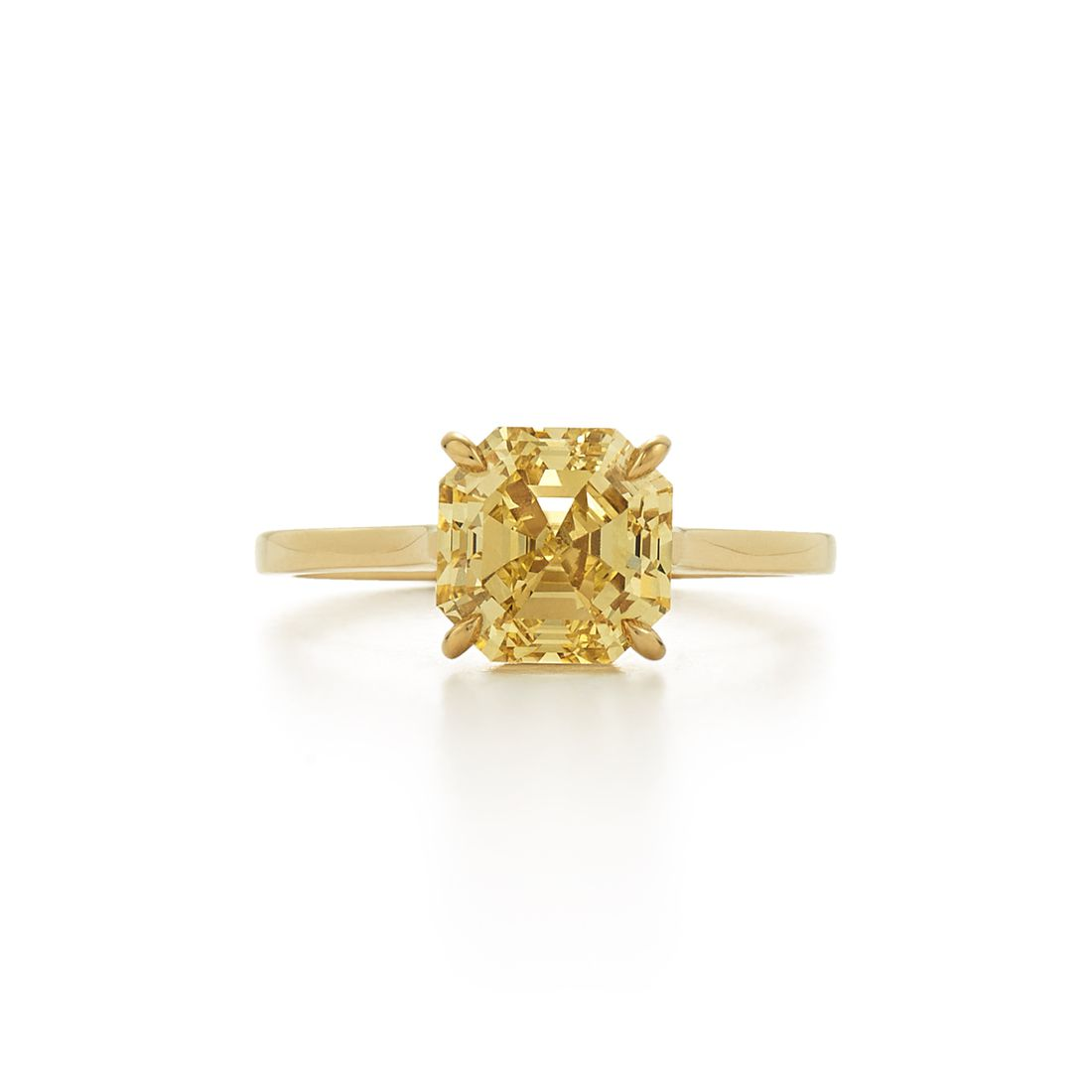 Yellow diamond engagement ring with yellow gold band on a white background