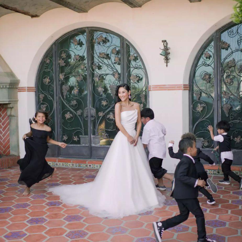 Ring bearers and flower girls running around the bride