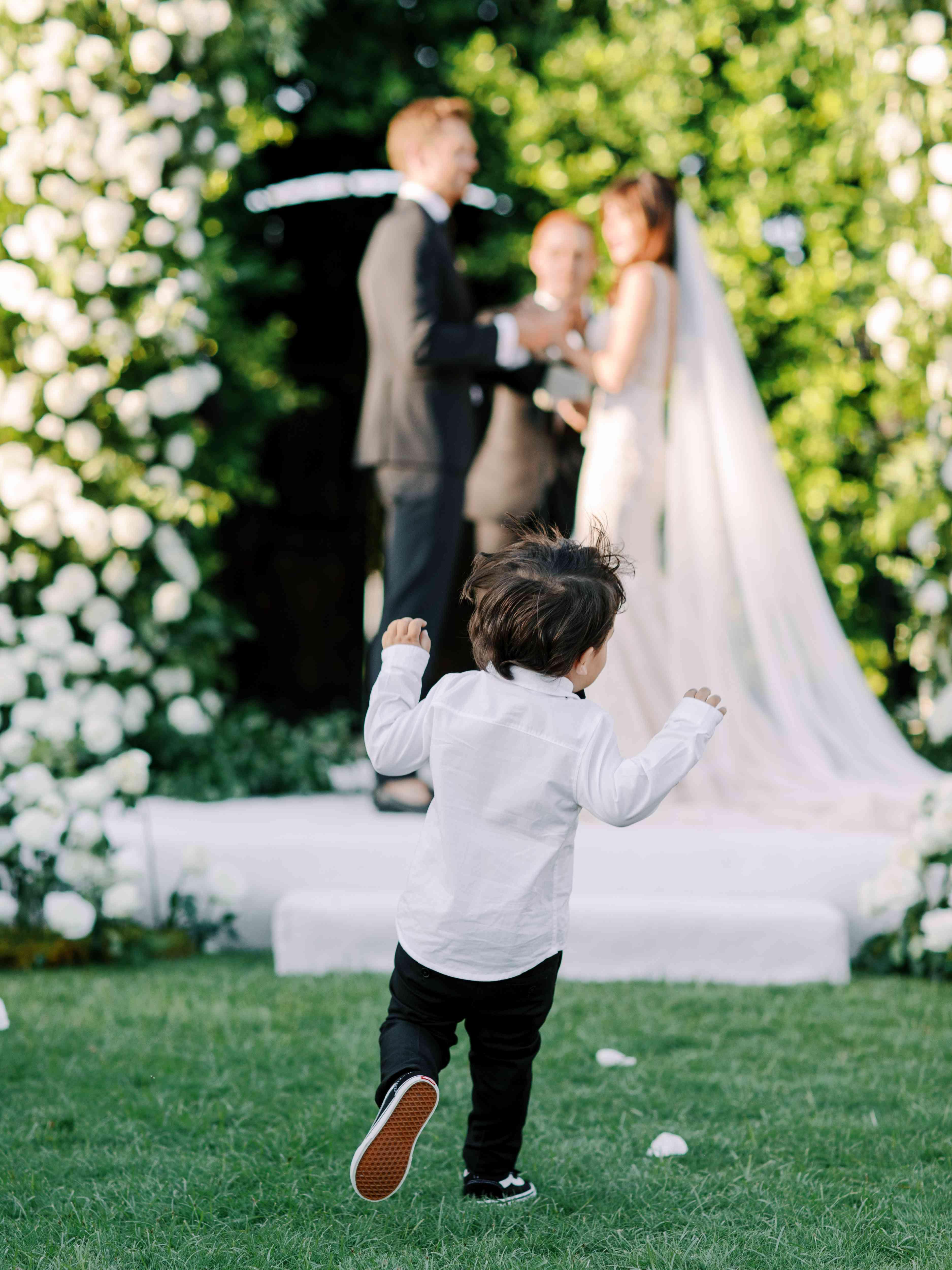 boy running down wedding aisle