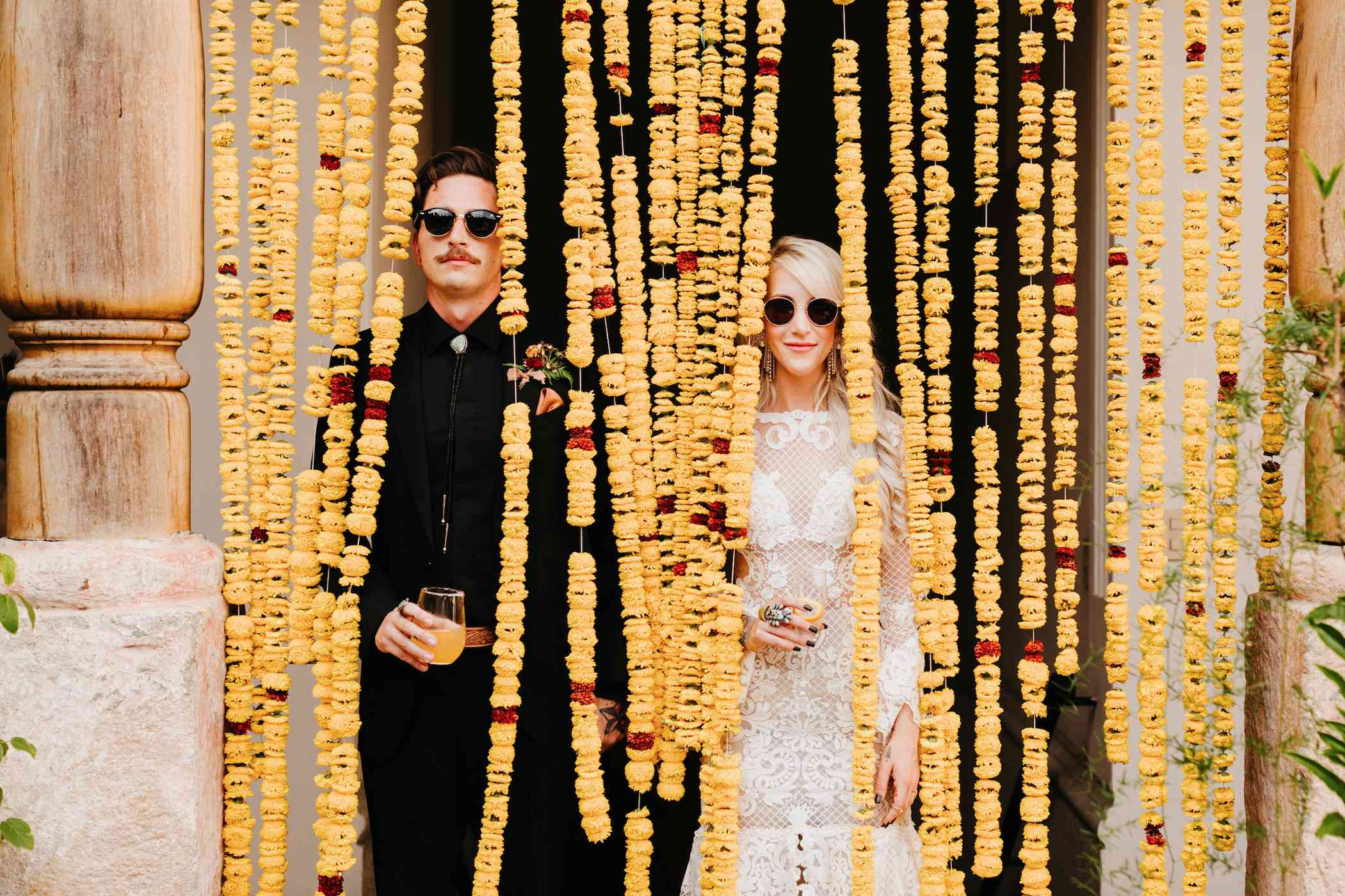 Newlyweds in front of yellow flower garlands