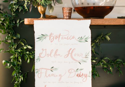Signature wedding cocktail menu hanging from mobile bar with vines