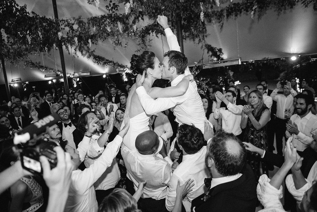 Bride and groom lifted on chairs at reception