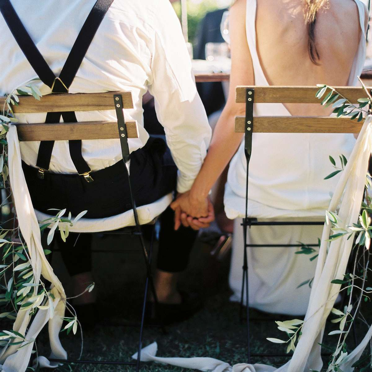 Bride and groom holding hands at dinner table