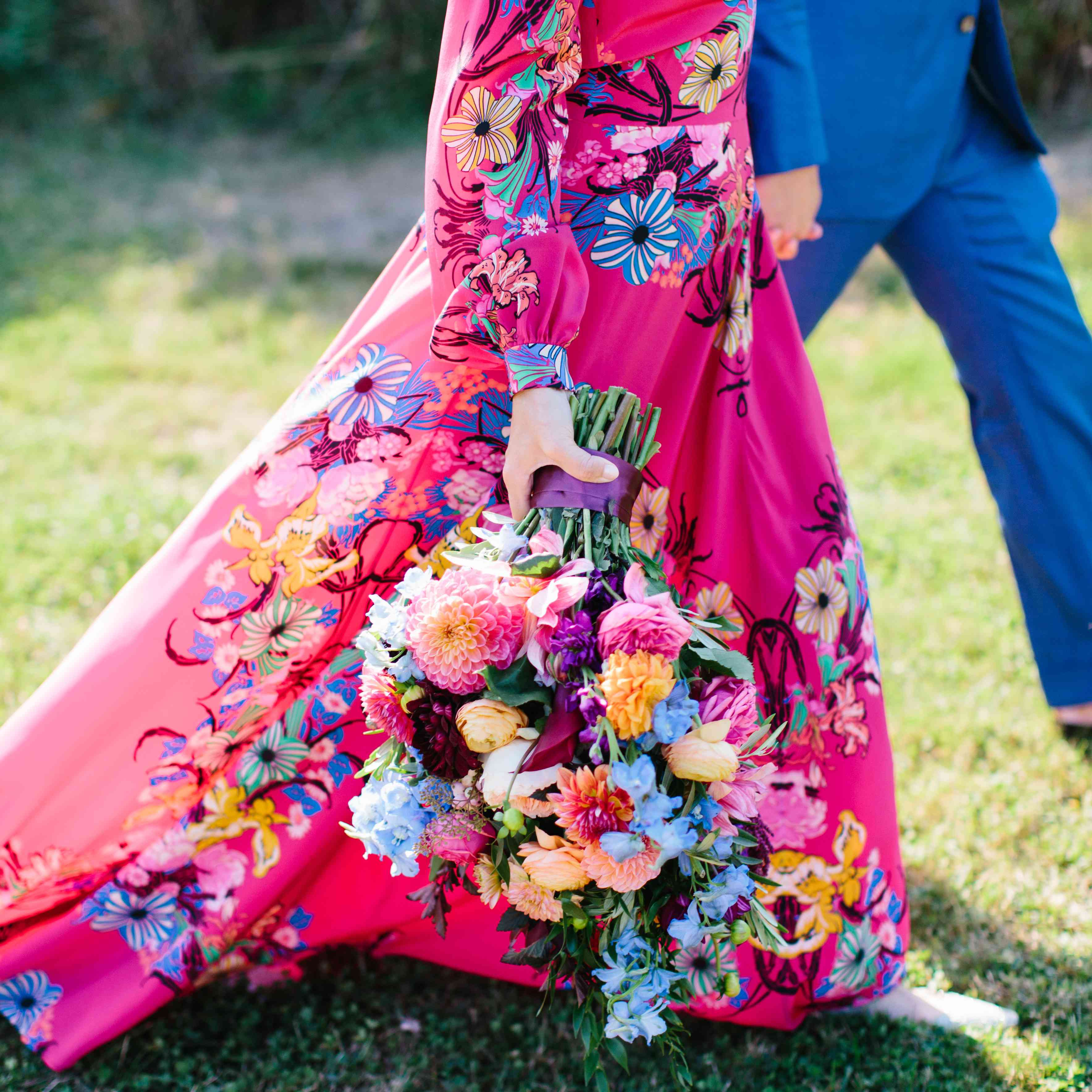 woman wearing colorful dress holding flowers