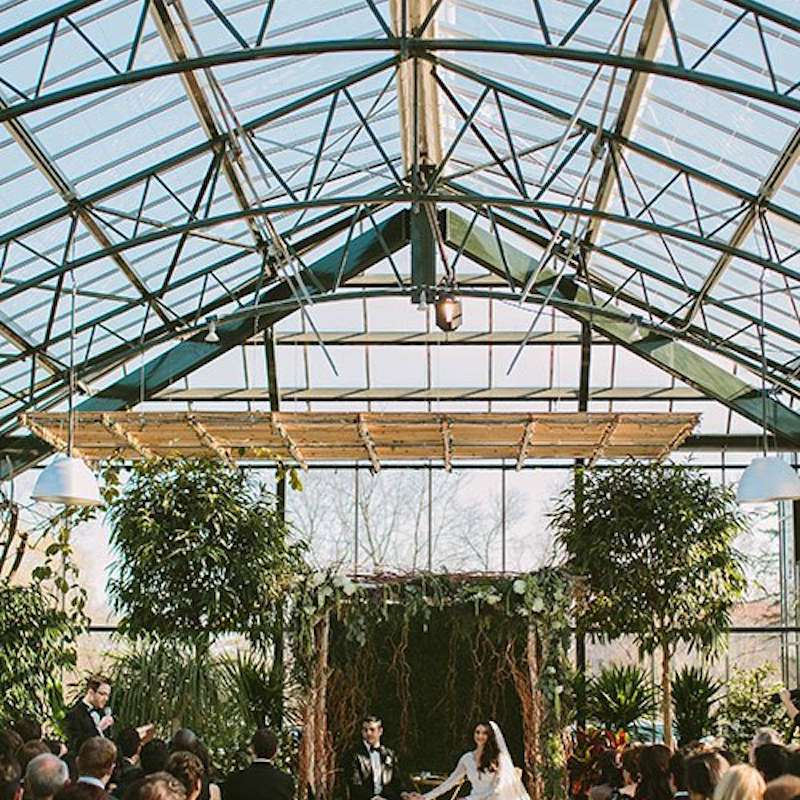 Couple seated during their wedding ceremony at Planterra Conservatory in Michigan