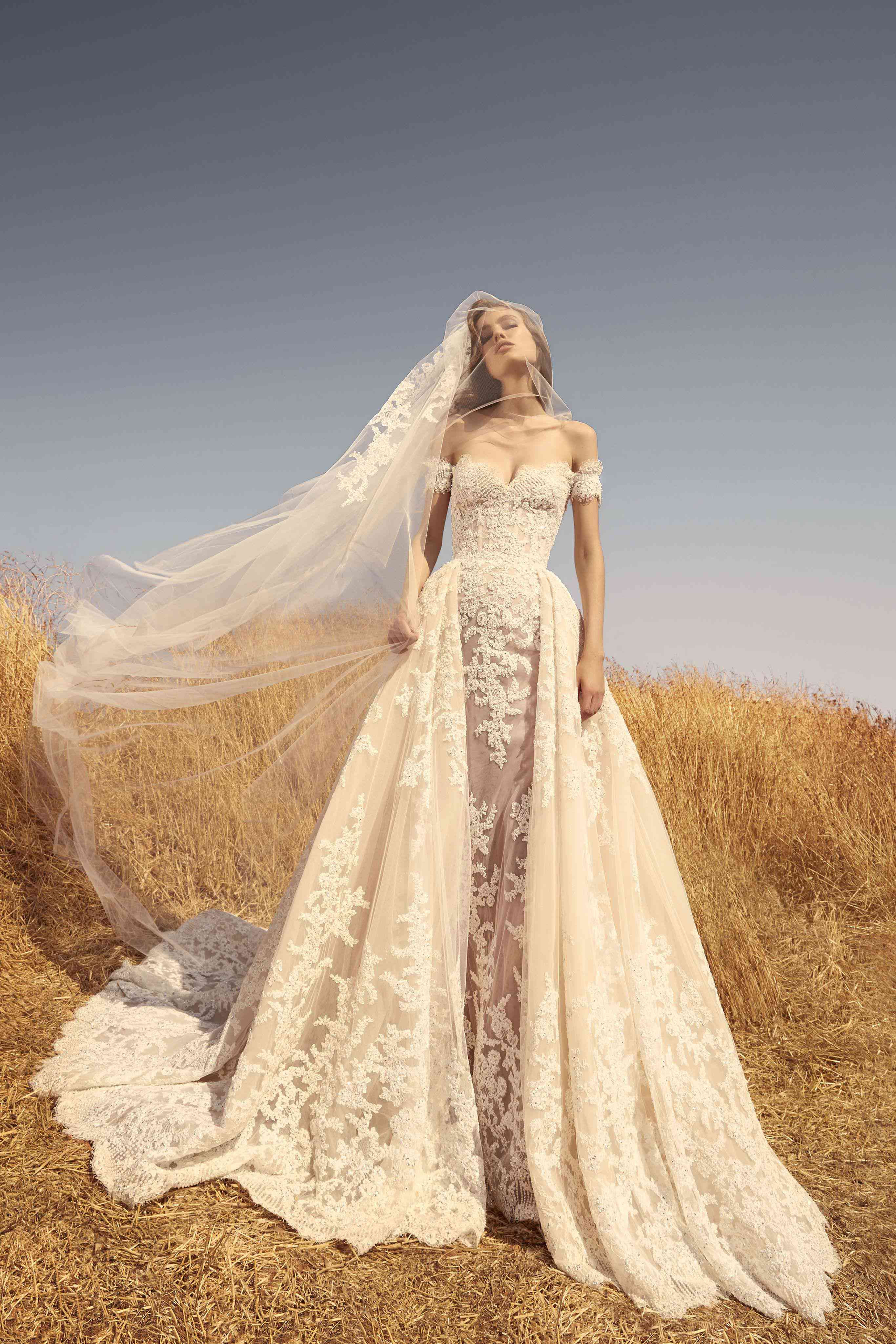 Model in n off-shoulder shell tulle dress decorated with embroidered off-white lace appliqués and a matching veil