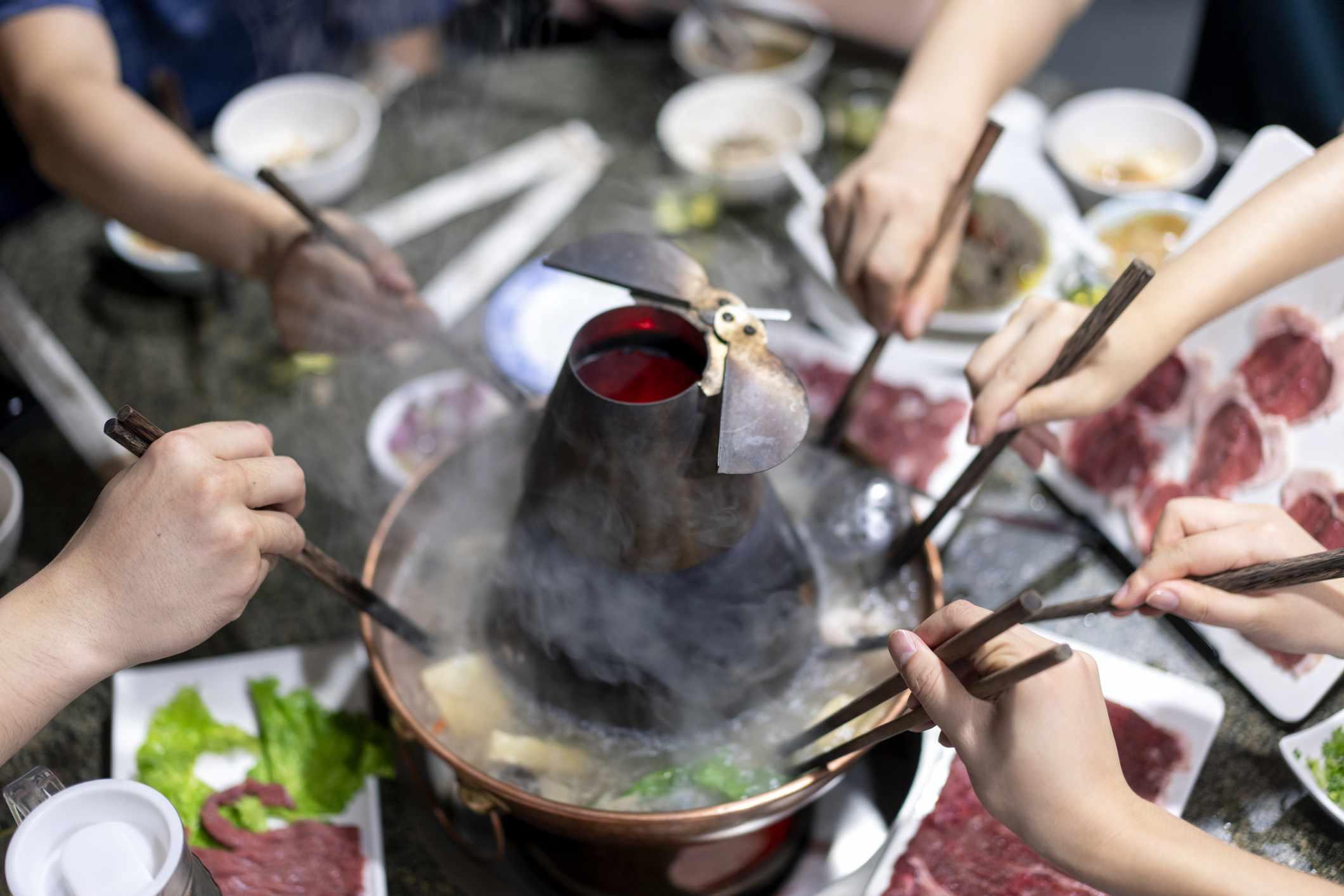 Friends enjoying a hot pot in a restaurant