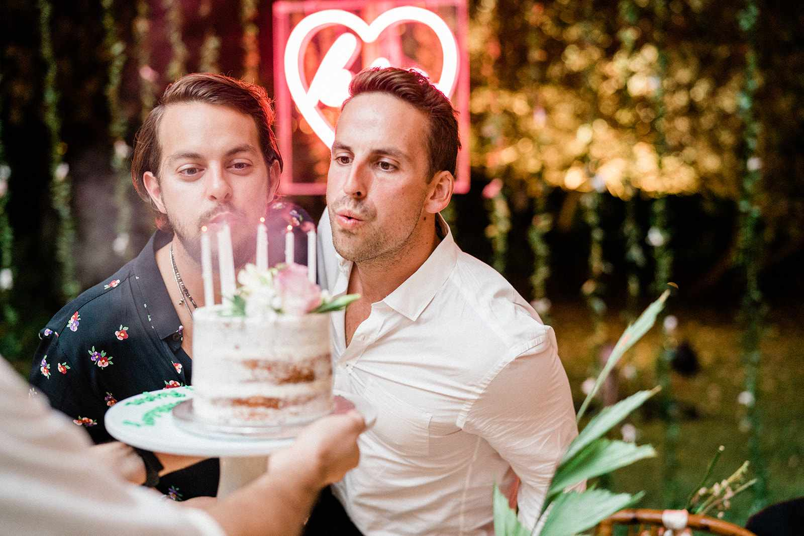 men blowing out birthday candles