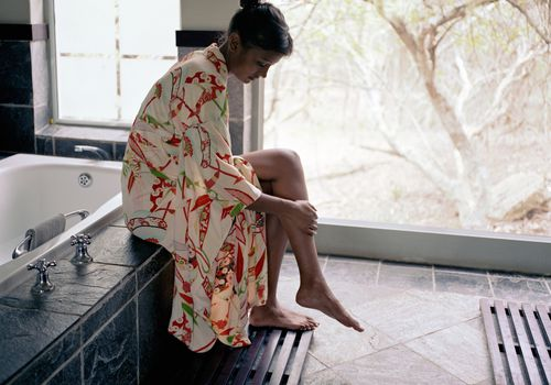 Girl in robe sitting on edge of tub putting lotion on legs
