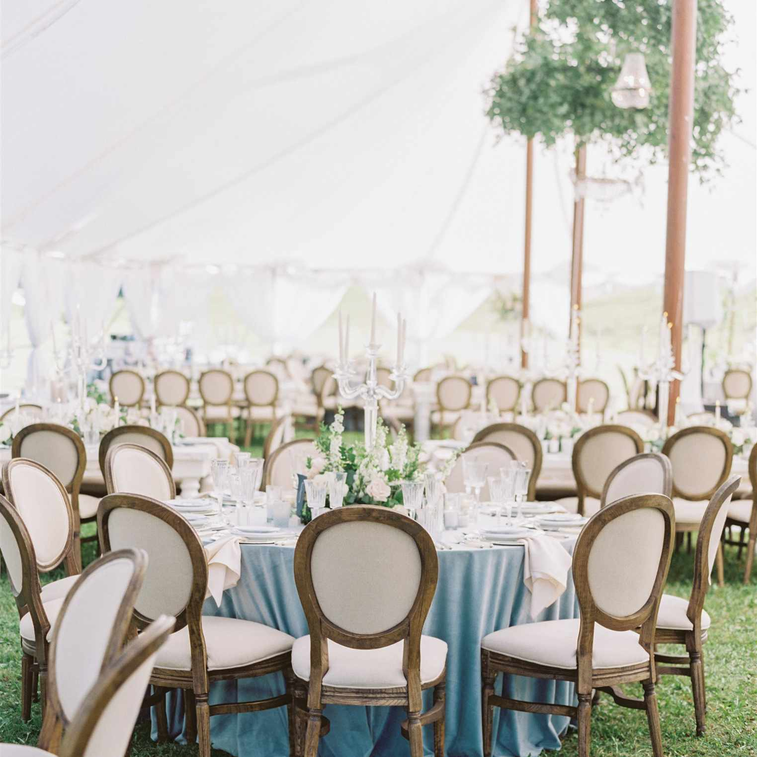 tables under a tent with greenery