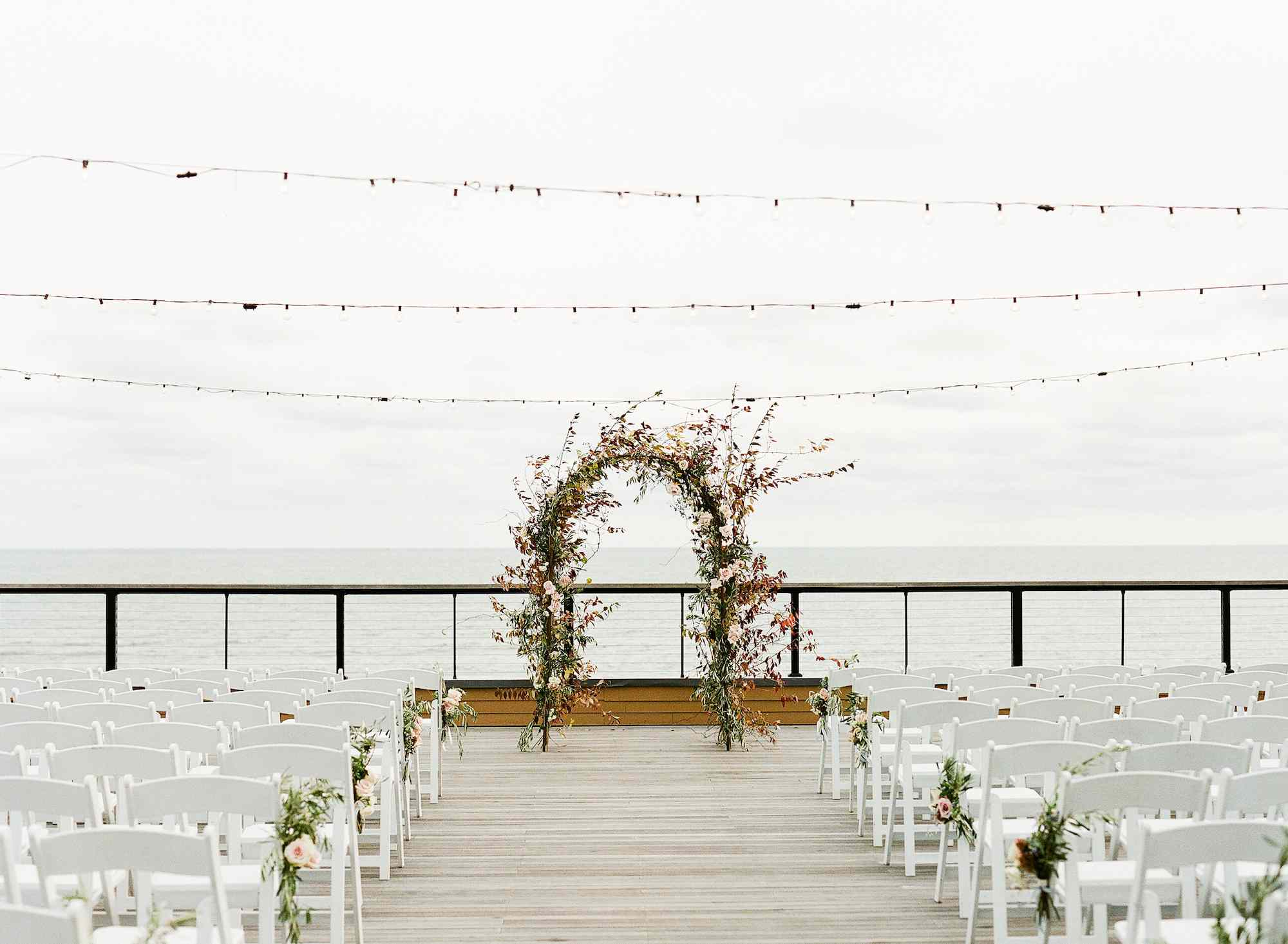 A seaside ceremony with an arch of autumn leaves and roses