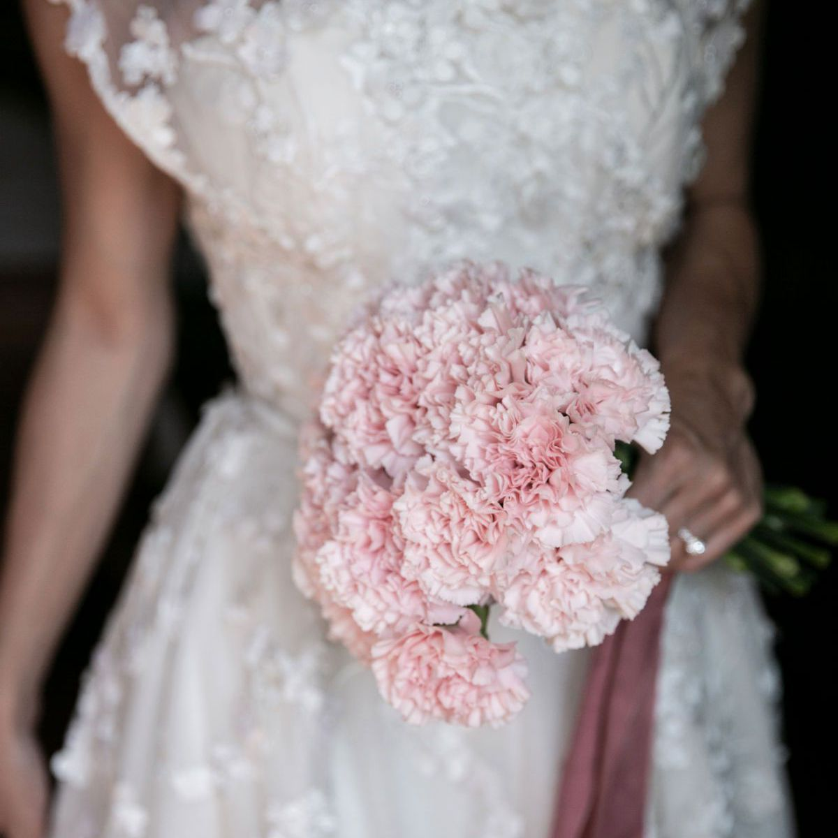 Bride holding posy bouquet of pink carnations