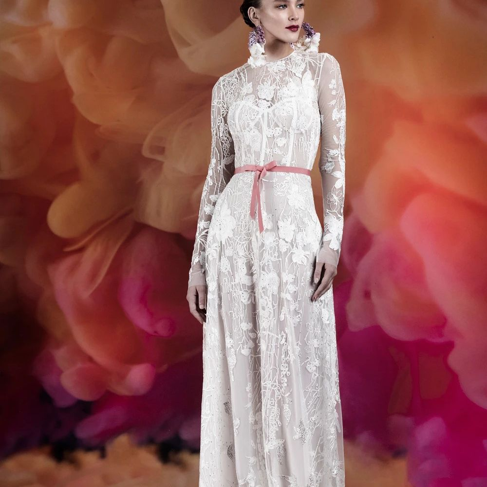 Model in long-sleeve embroidered lace gown with pink belt