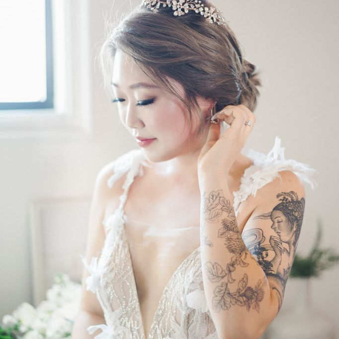 Tattooed bride wearing a whimsical feathered gown
