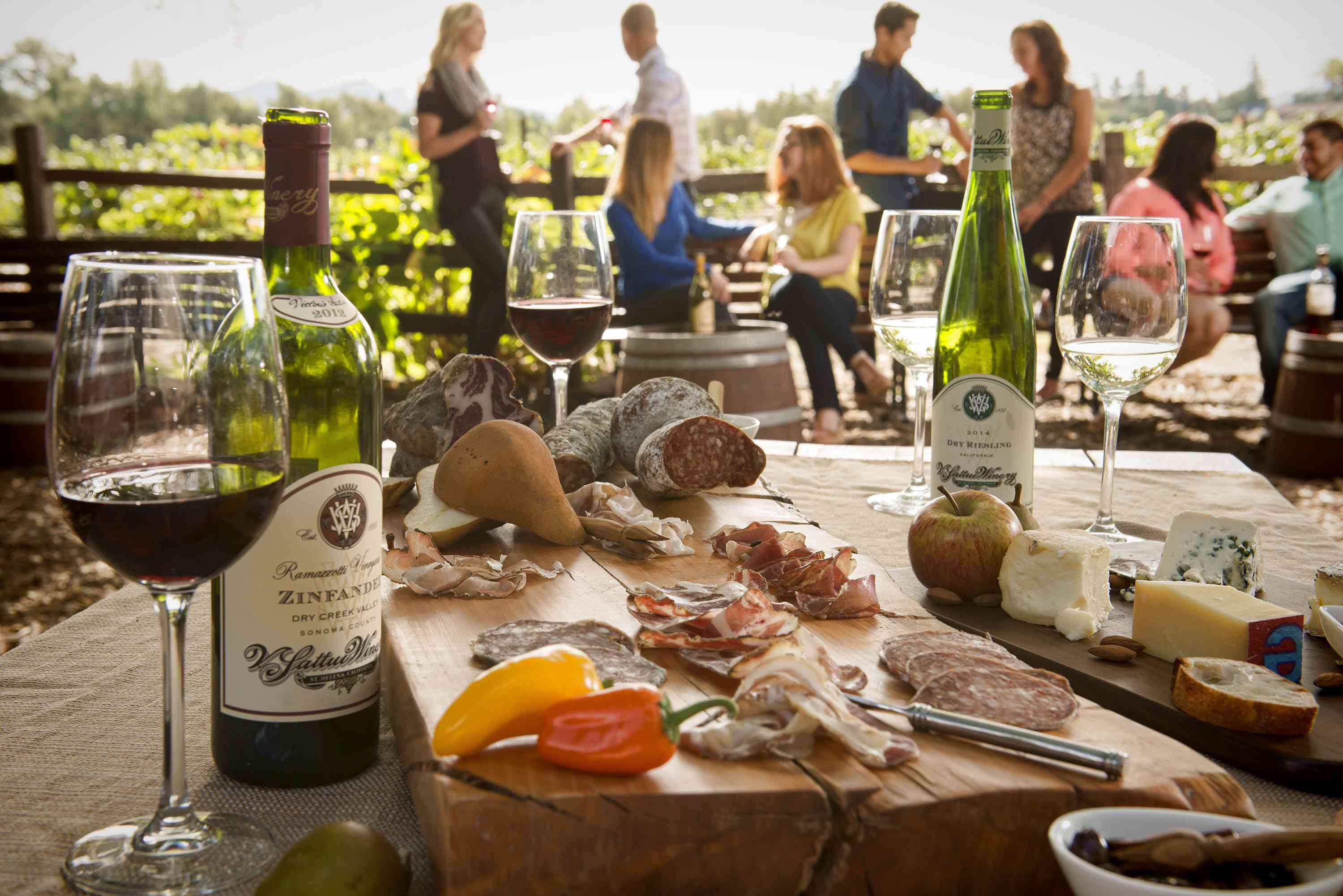 A table with wine and charcuterie with a group of people in the background