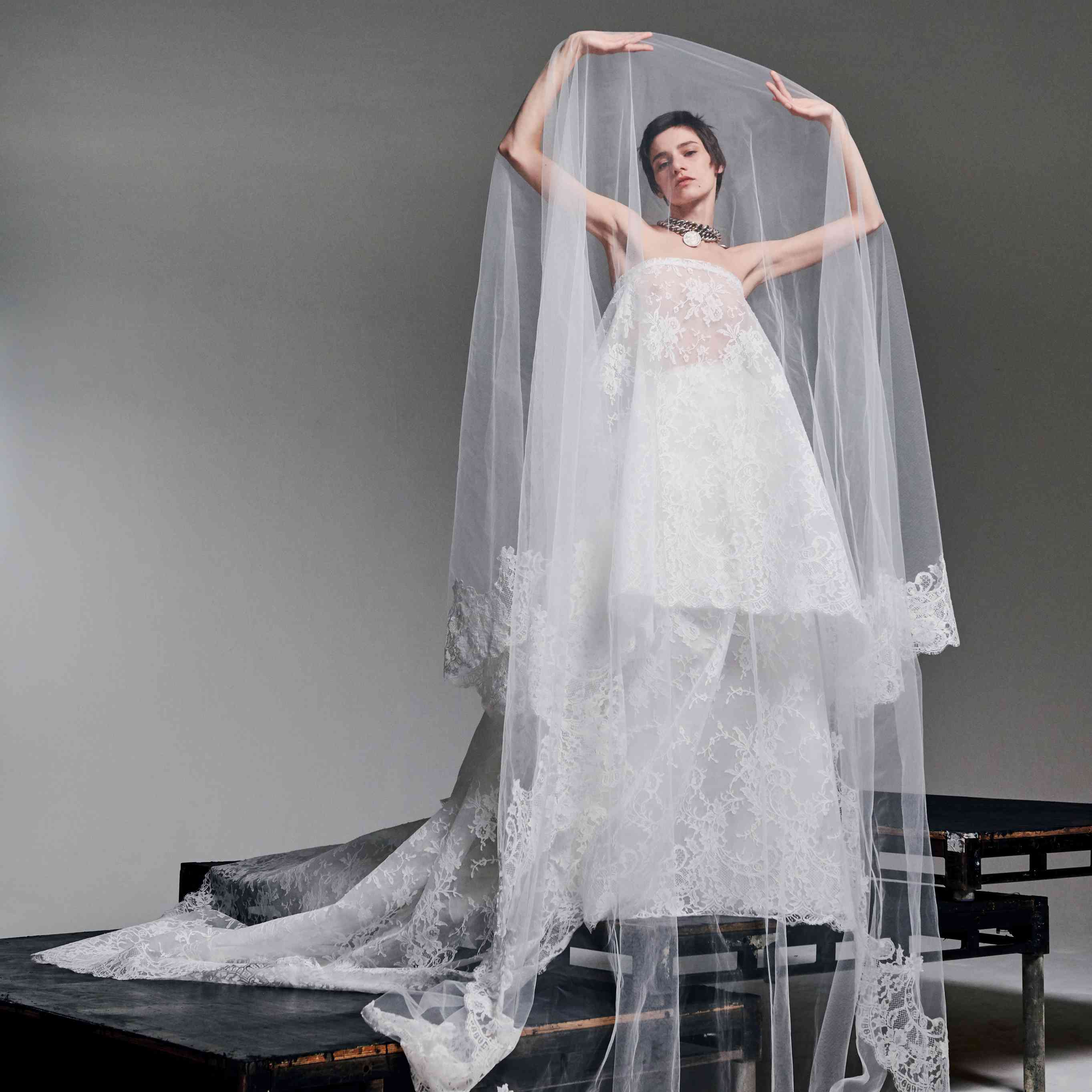 Model in strapless lace gown with large veil