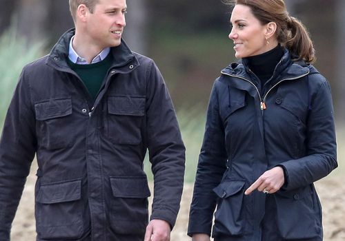 Prince William (left) and Kate Middleton walking outside and looking at each other