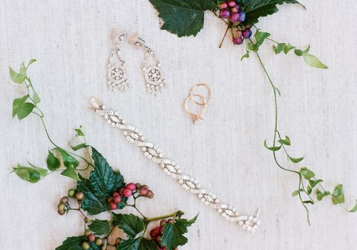Bridal jewelry and wedding rings beside two plants