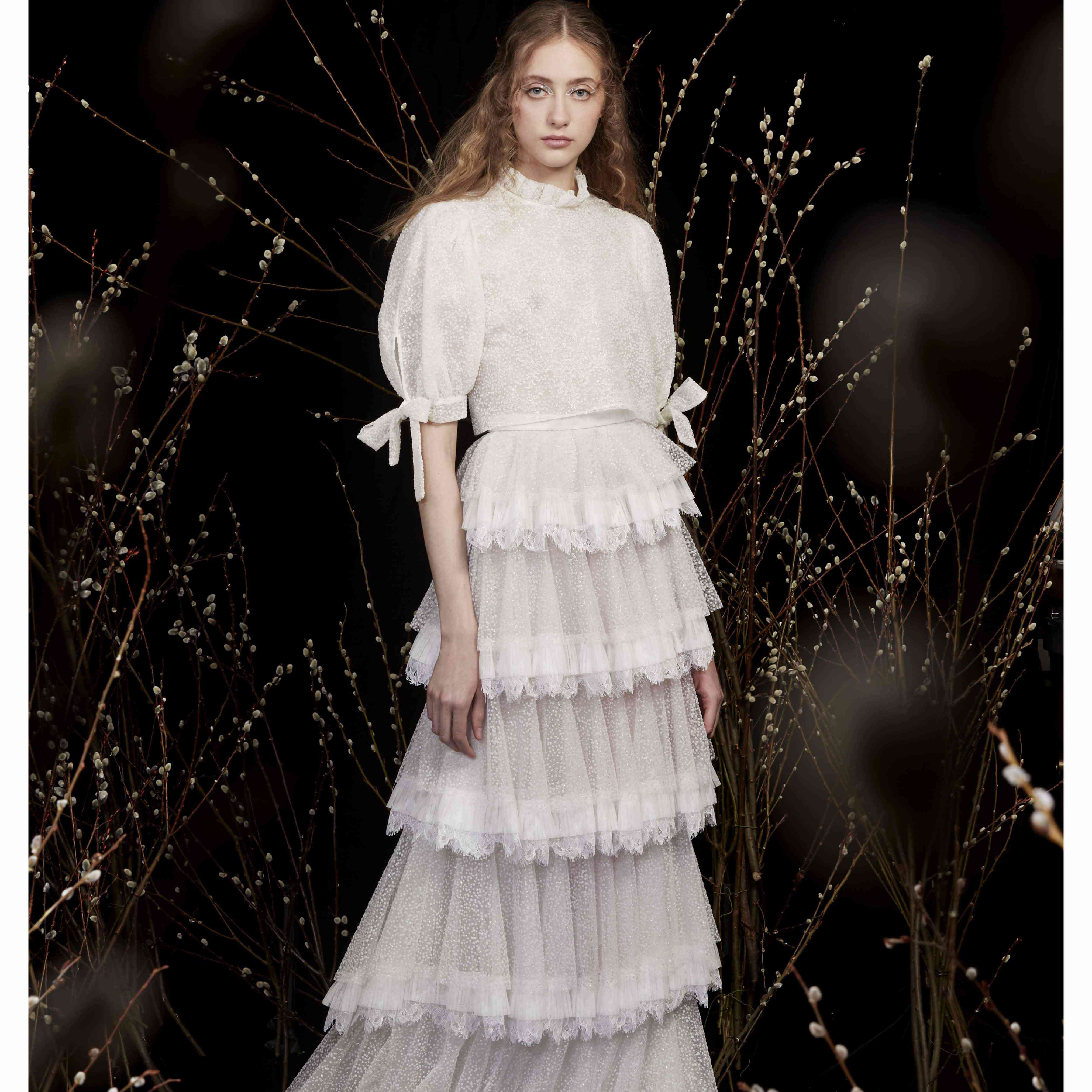 Model in ruffle neck blouse and tiered lace skirt