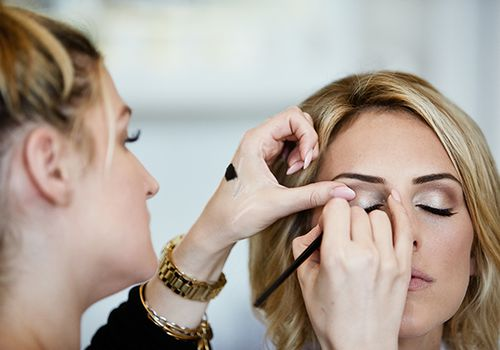 Close-up of woman doing another woman's eye makeup