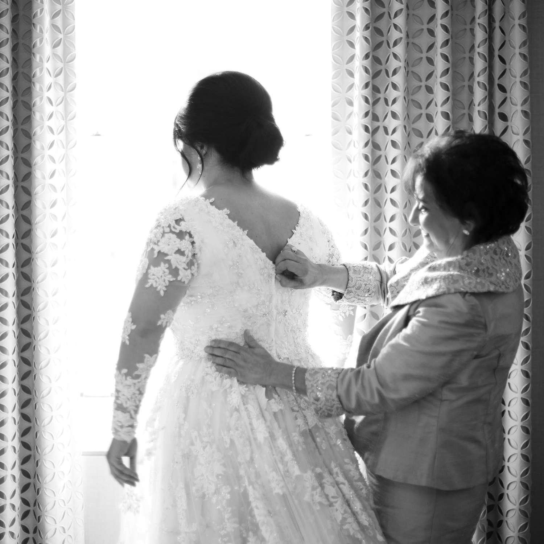 <p>mom helping bride zip up wedding dress</p><br><br>