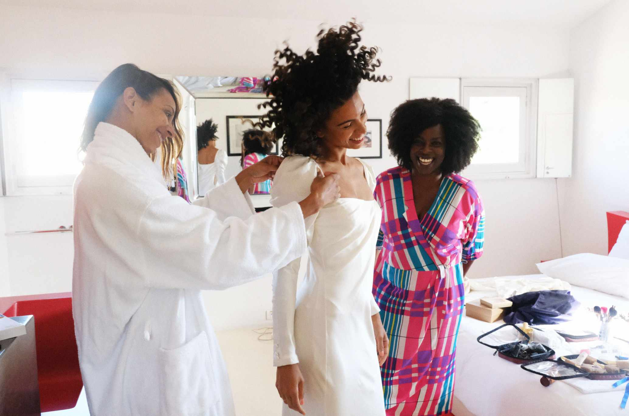 Happy bride getting into dress