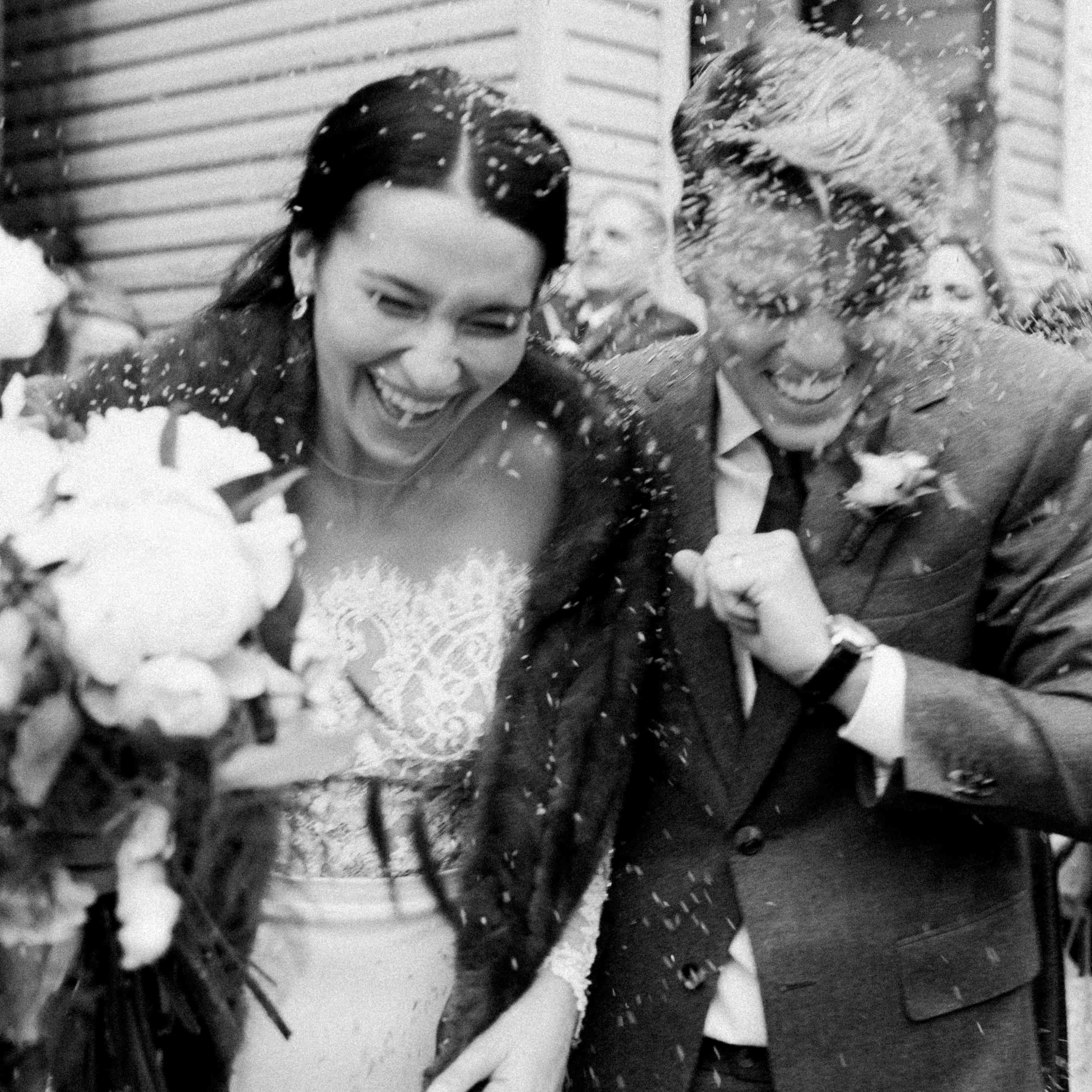 Bride and groom under rice toss