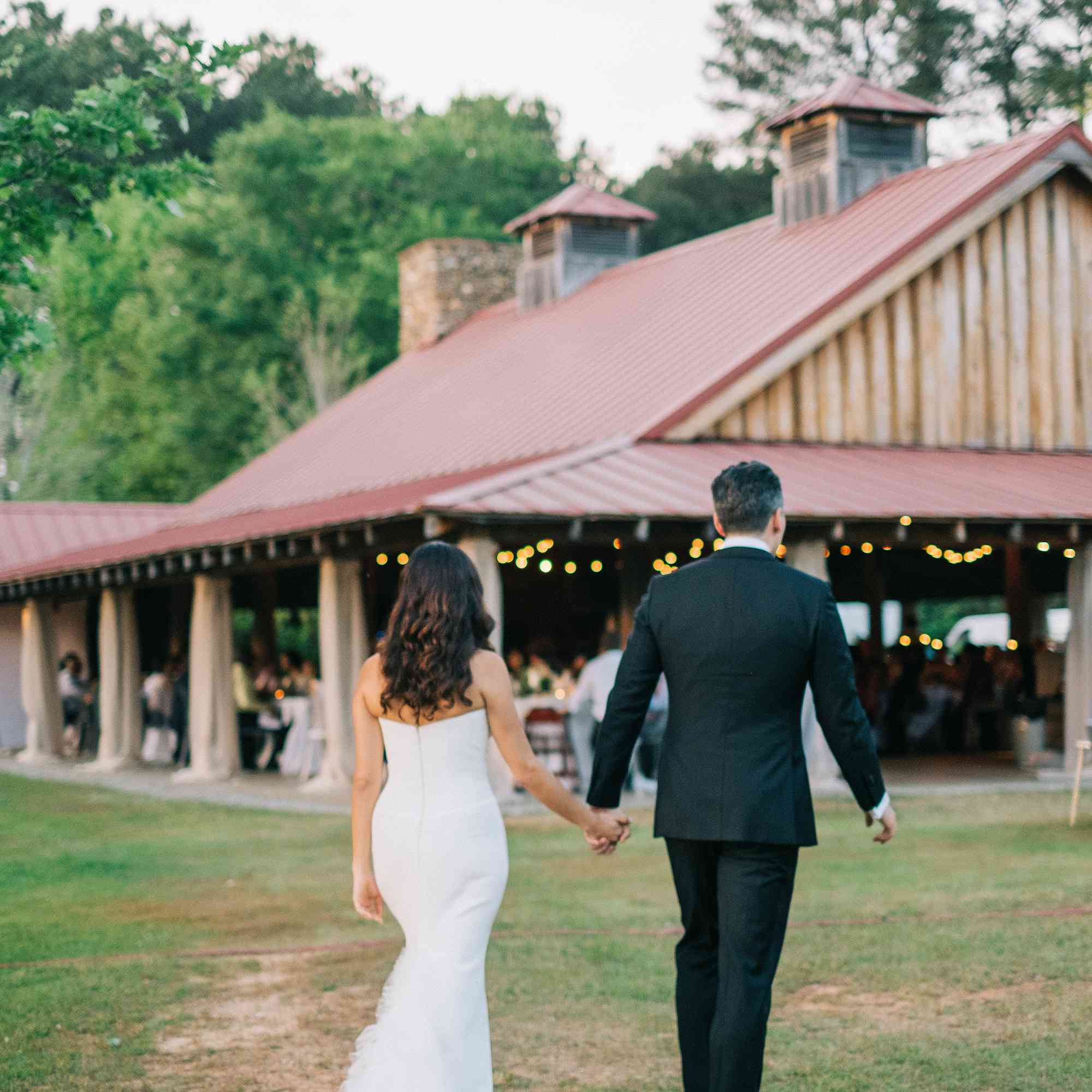 Bride and groom holding hands walking to barn