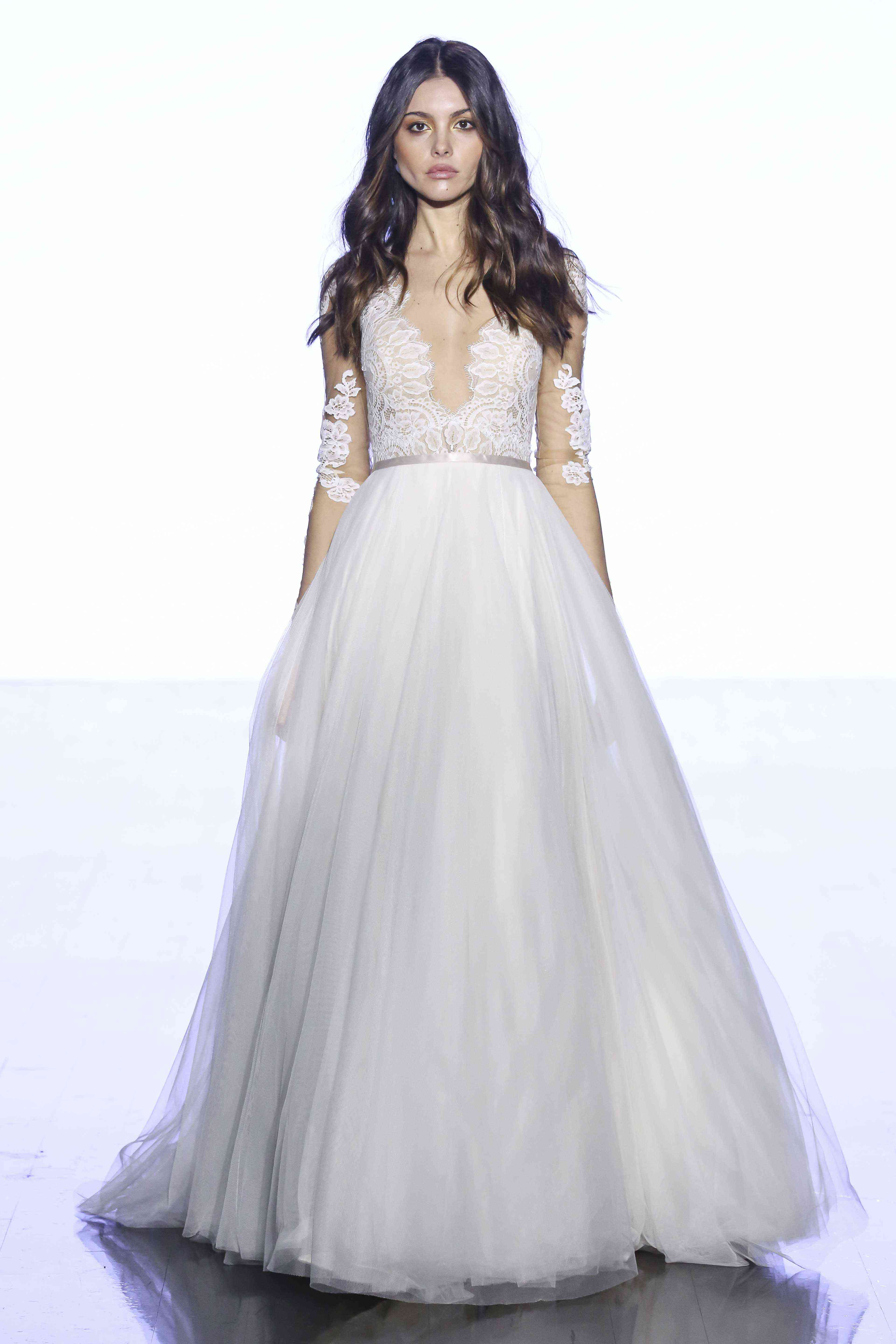 Model in A-line gown with a lace-accented long-sleeve illusion tulle bodice and a full net skirt with a satin waistband