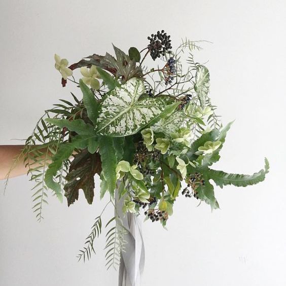 An intricate green bouquet with gray ribbon.