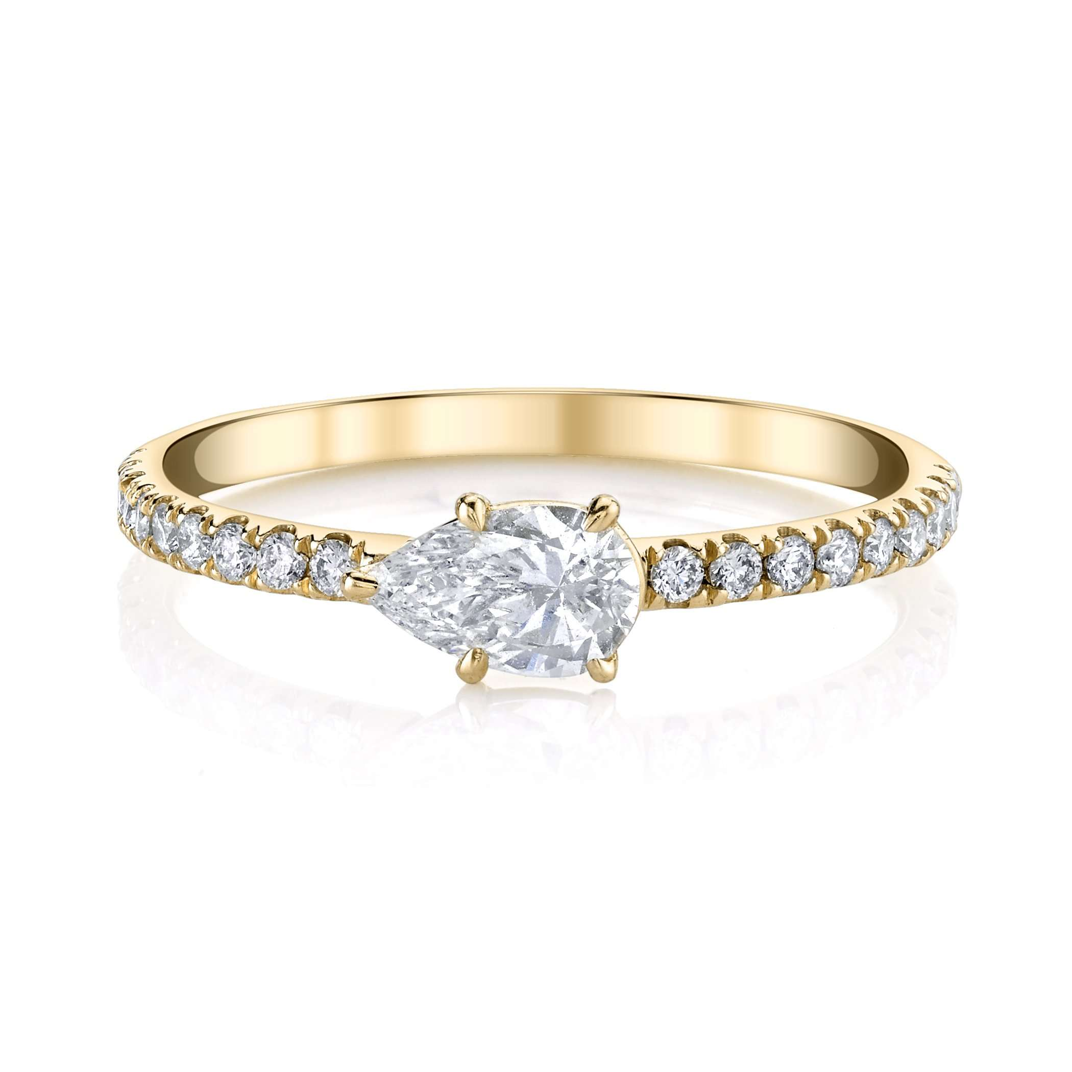 East-west pear diamond engagement ring with yellow gold eternity band on a white background