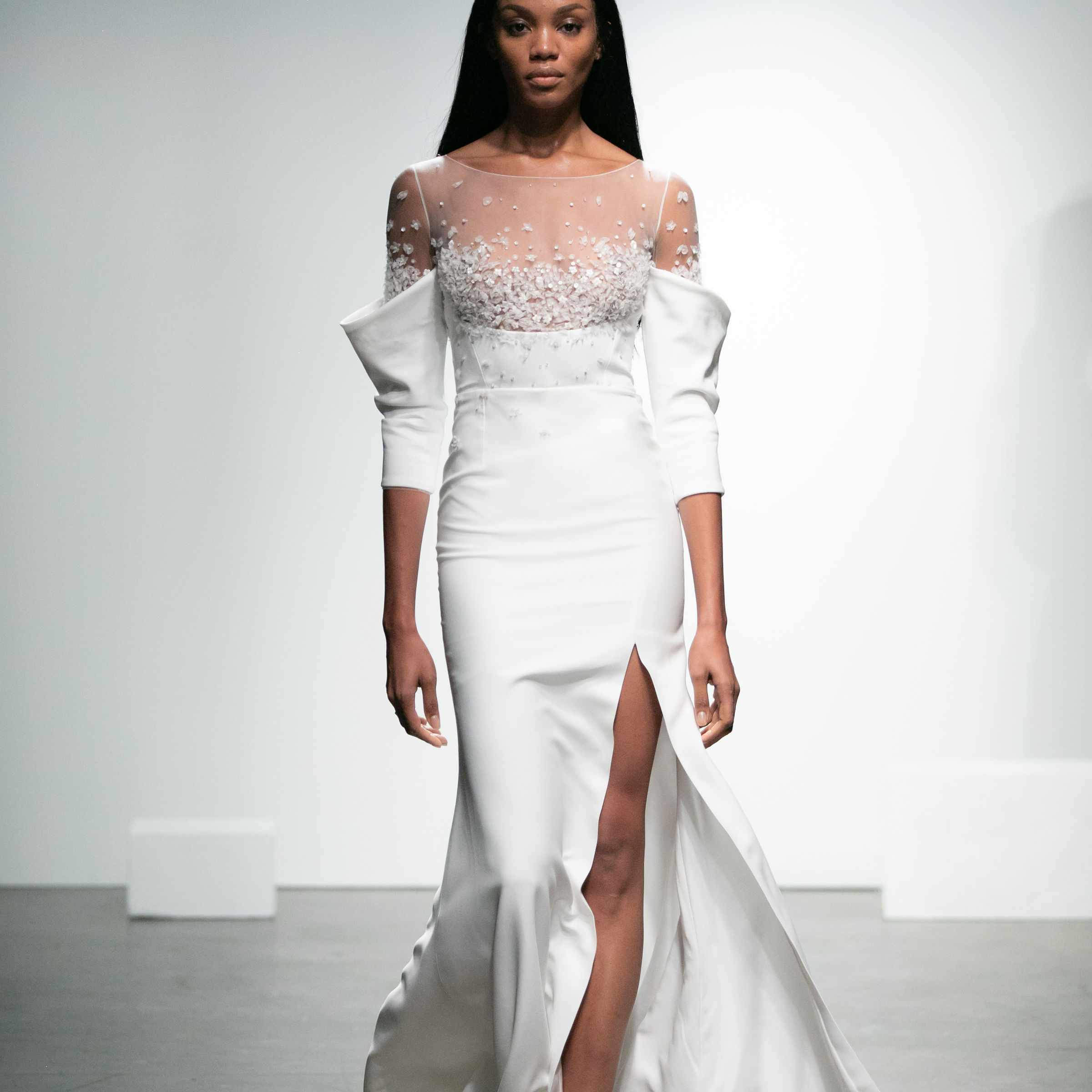 Model in crepe dress with roll-up effect sleeves and embroidered tulle neckline with skirt slit