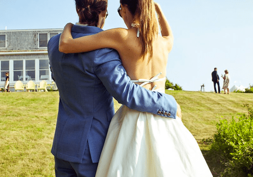 A bride and groom embracing on a lawn at their wedding.