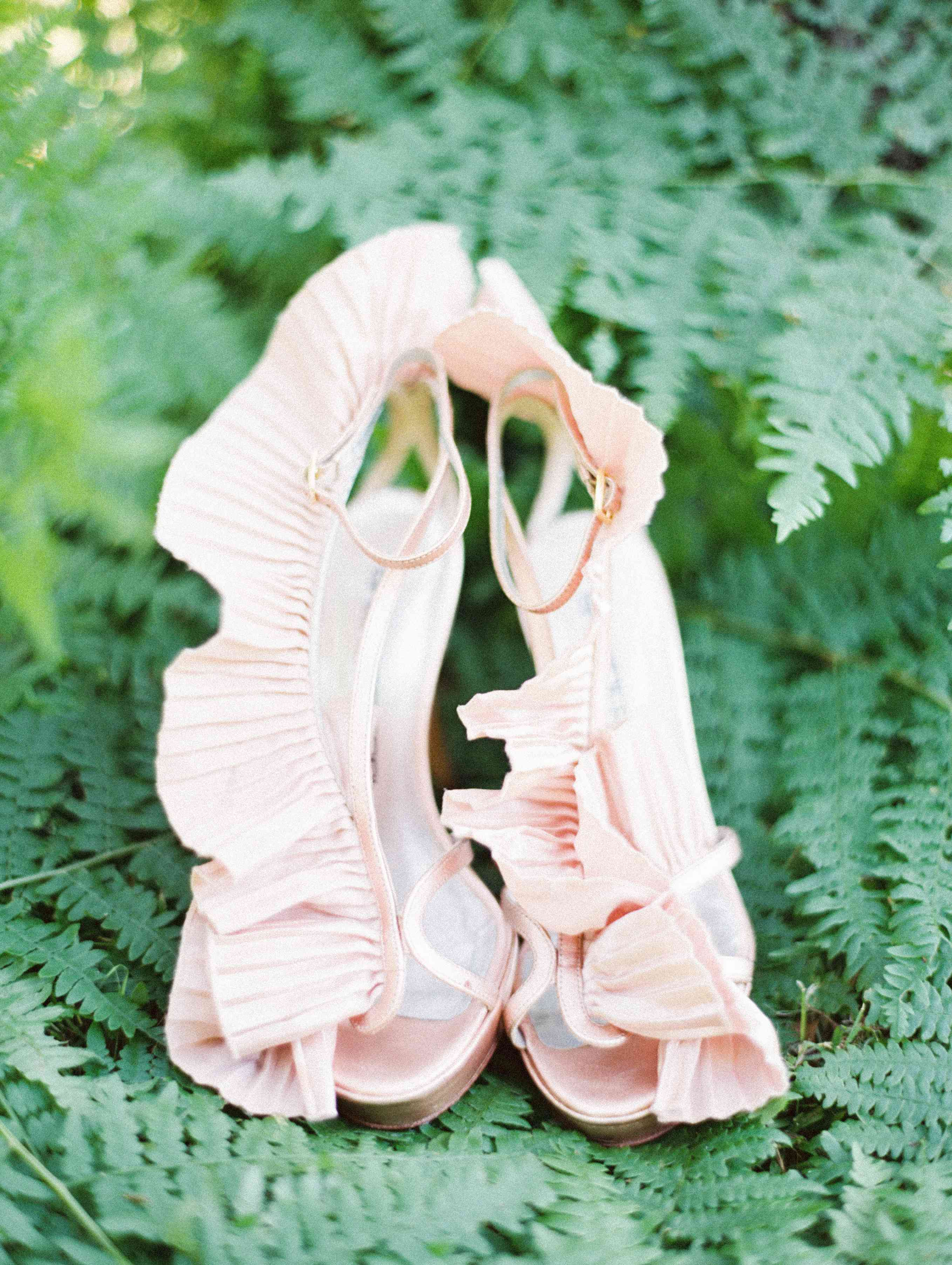 A pair of delicate pink heels with ruffled fabric.