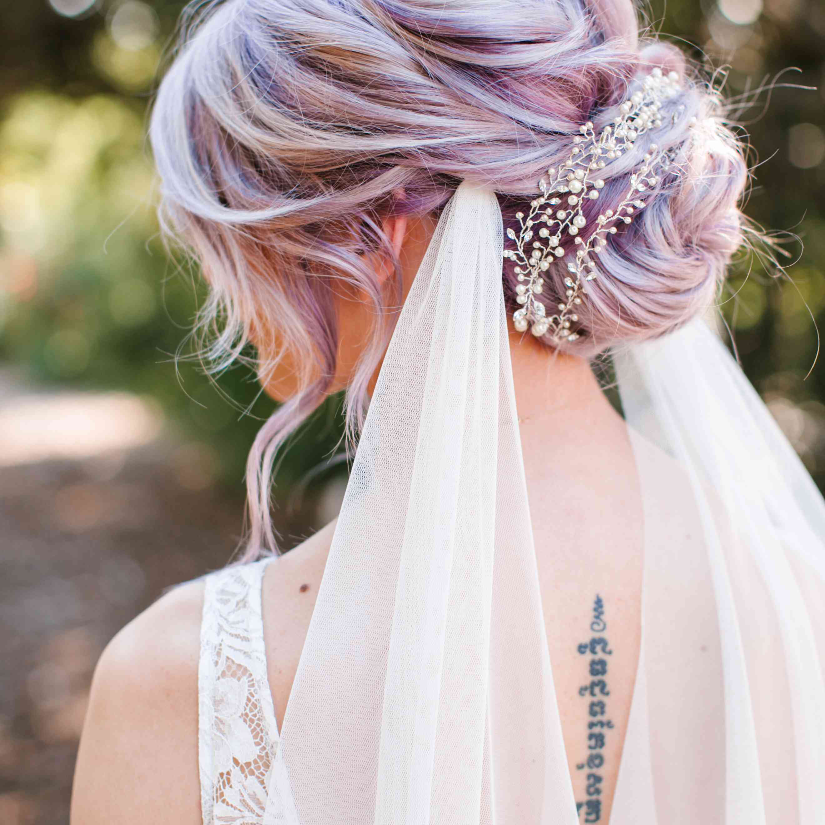 Close up of bride with lavender hair in bun with pearl pin