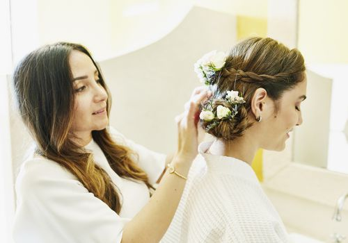 bride getting hair done by stylist for wedding