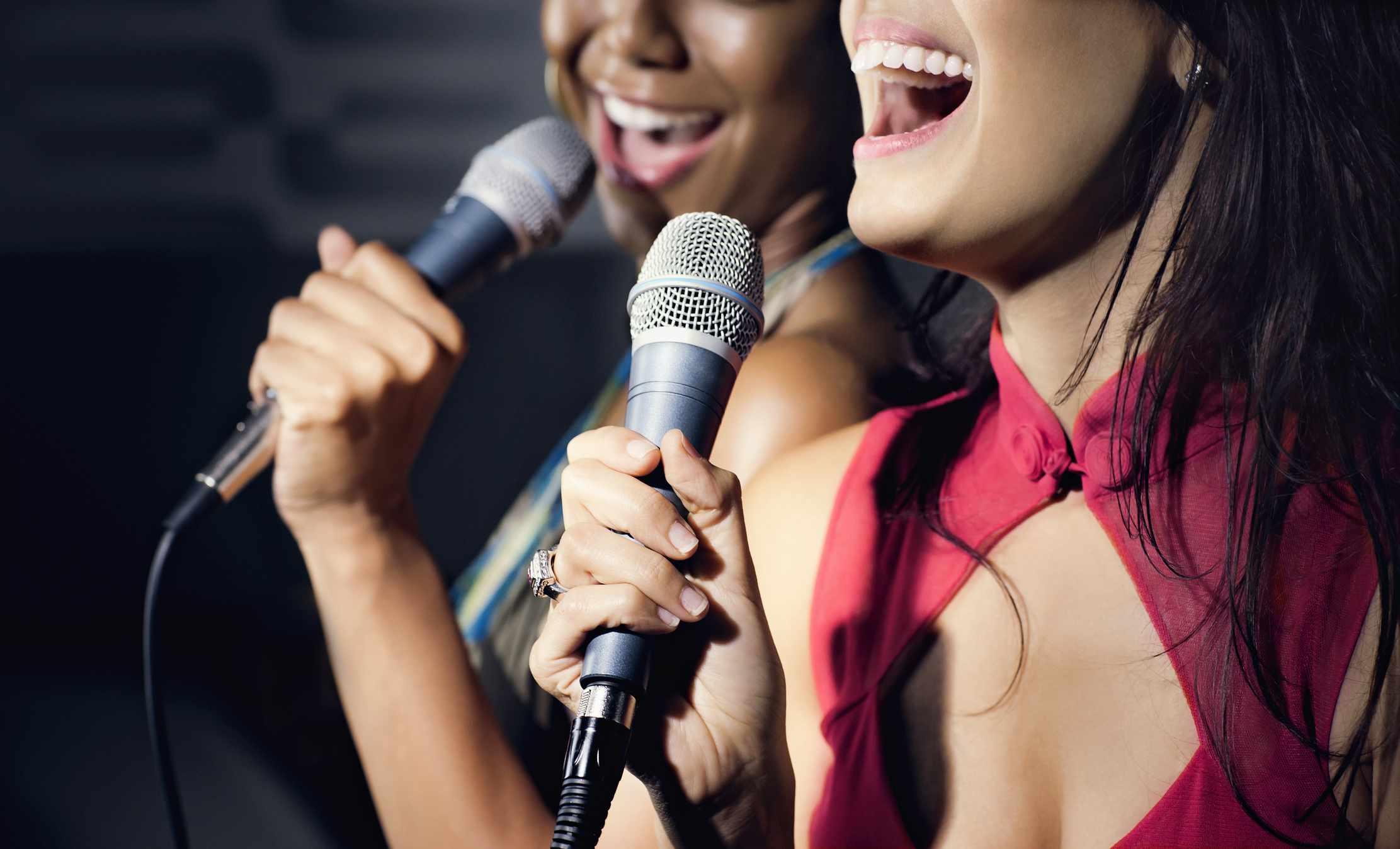 Two women sing karaoke
